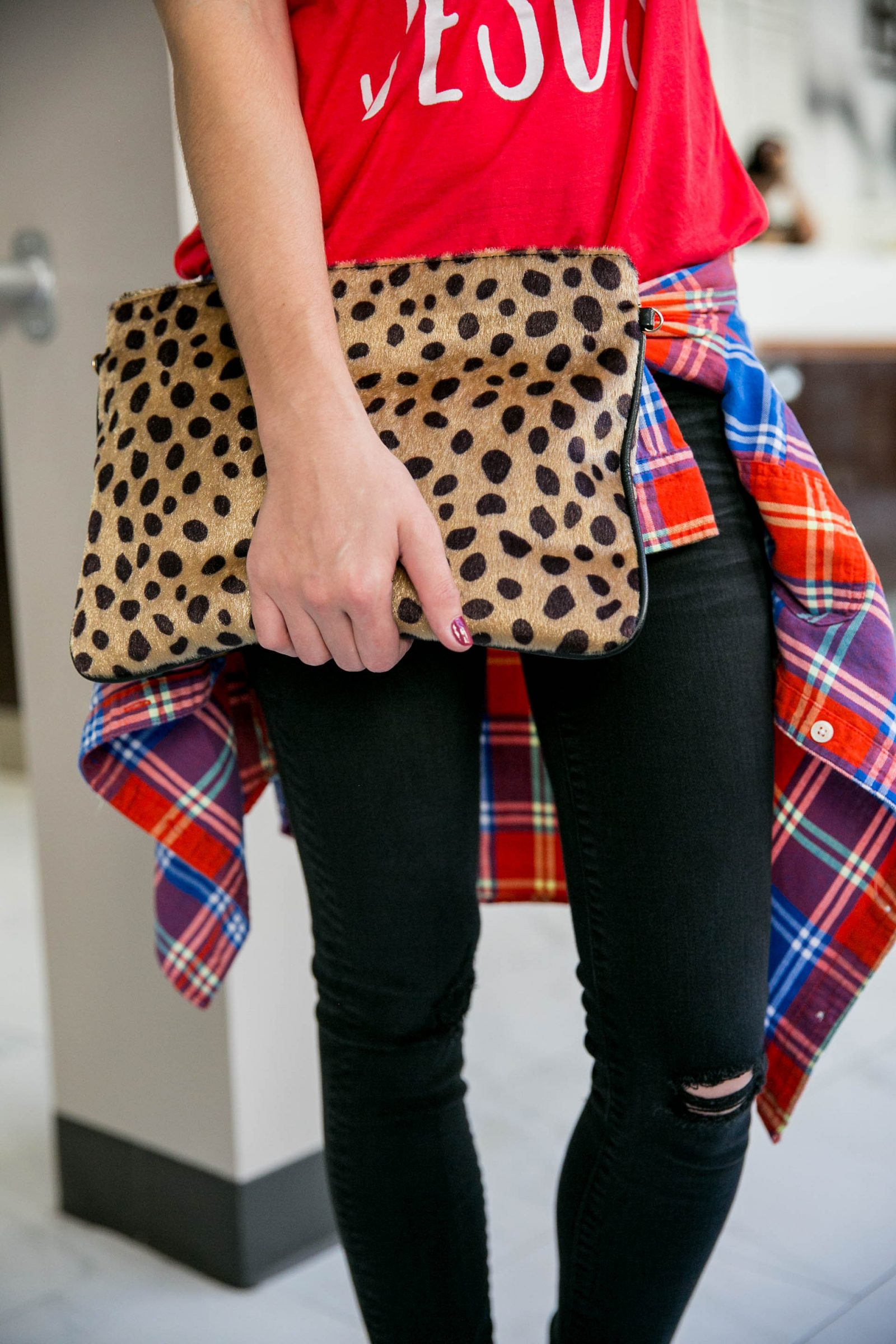 Houston fashion blogger Uptown with Elly Brown wears a leopard clutch with a plaid top