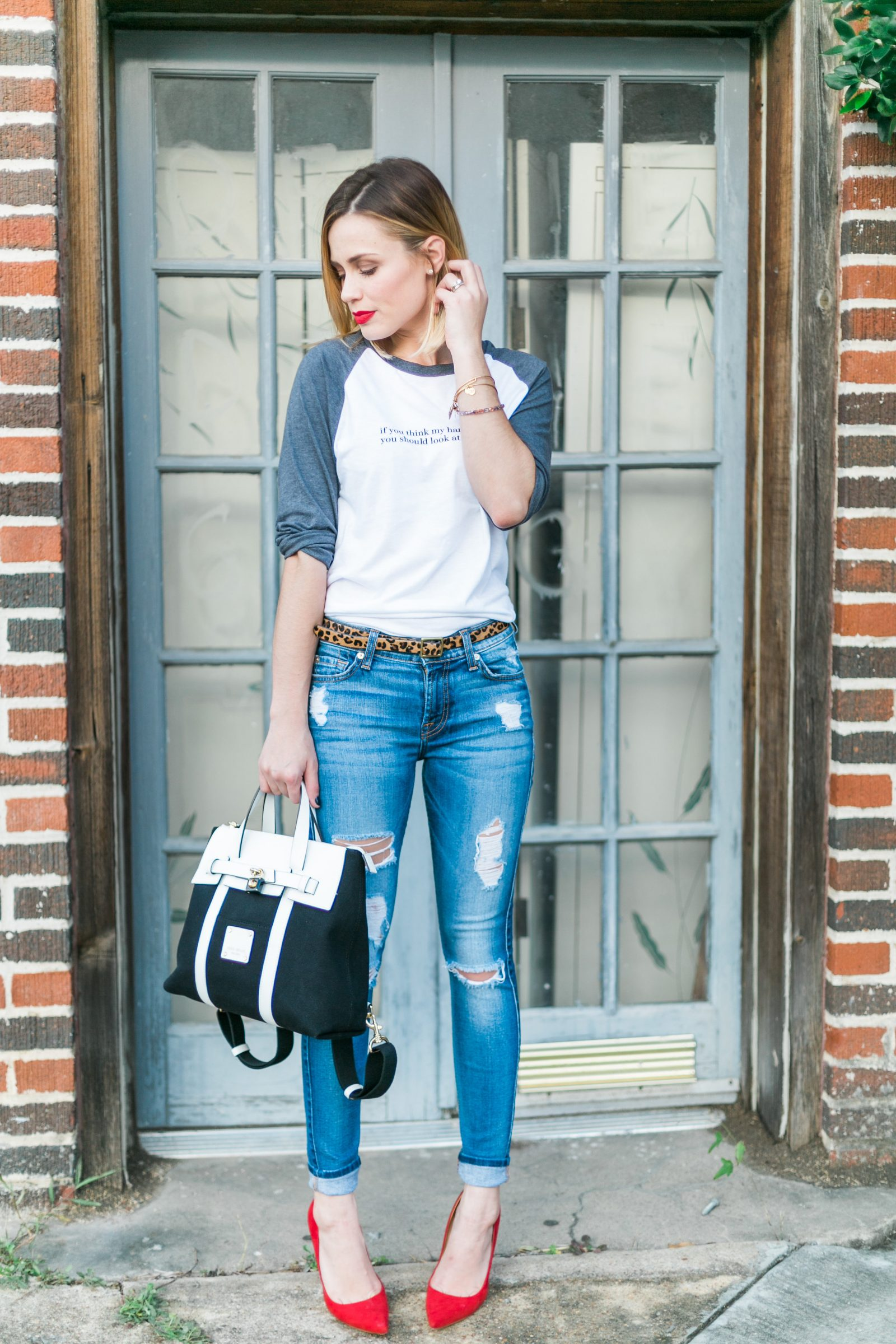 Houston fashion blogger wears a graphic tshirt and jeans outfit paired with red heels