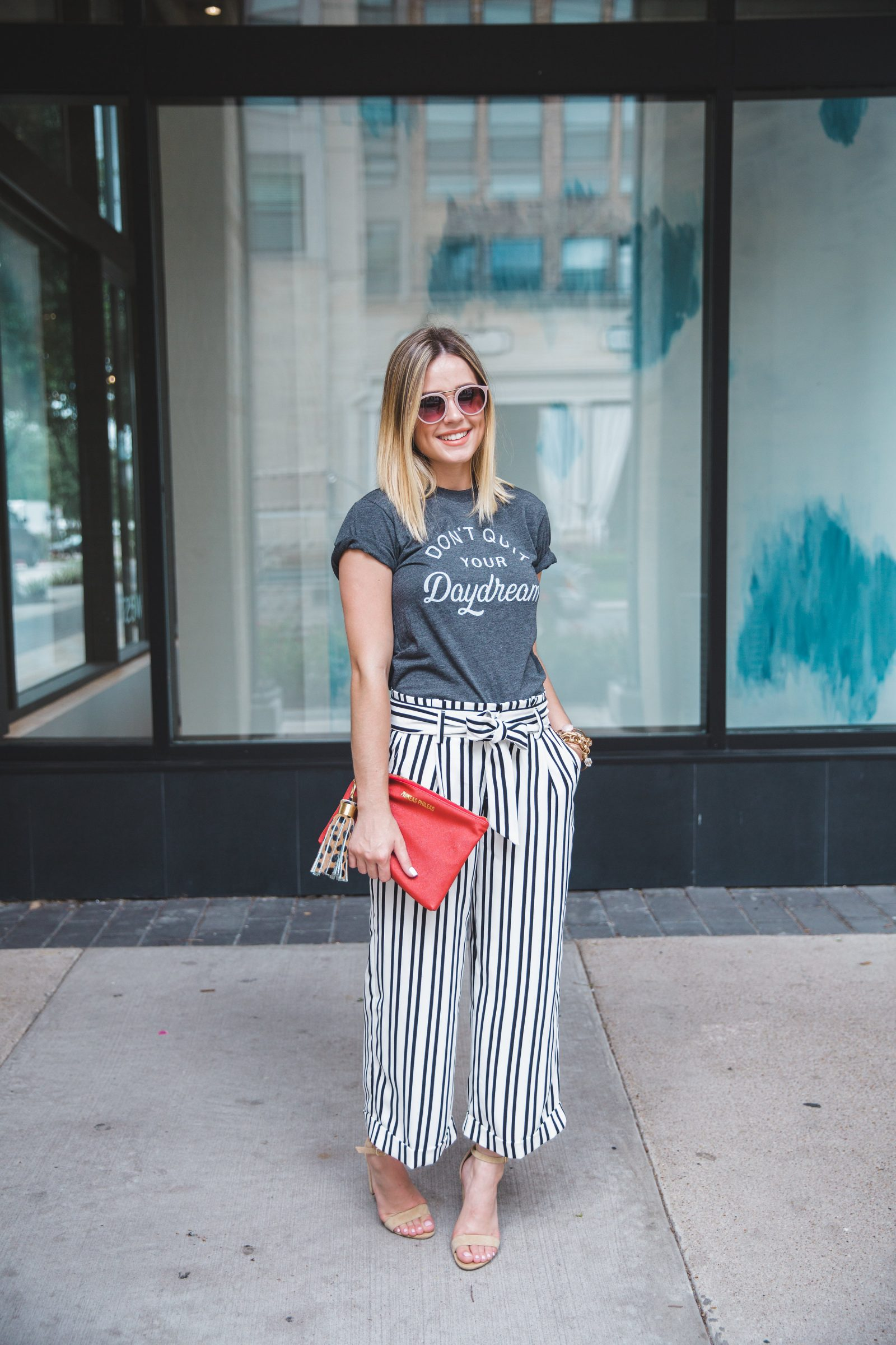 Houston fashion blogger Elly Brown wears a paper bag pants with a red clutch