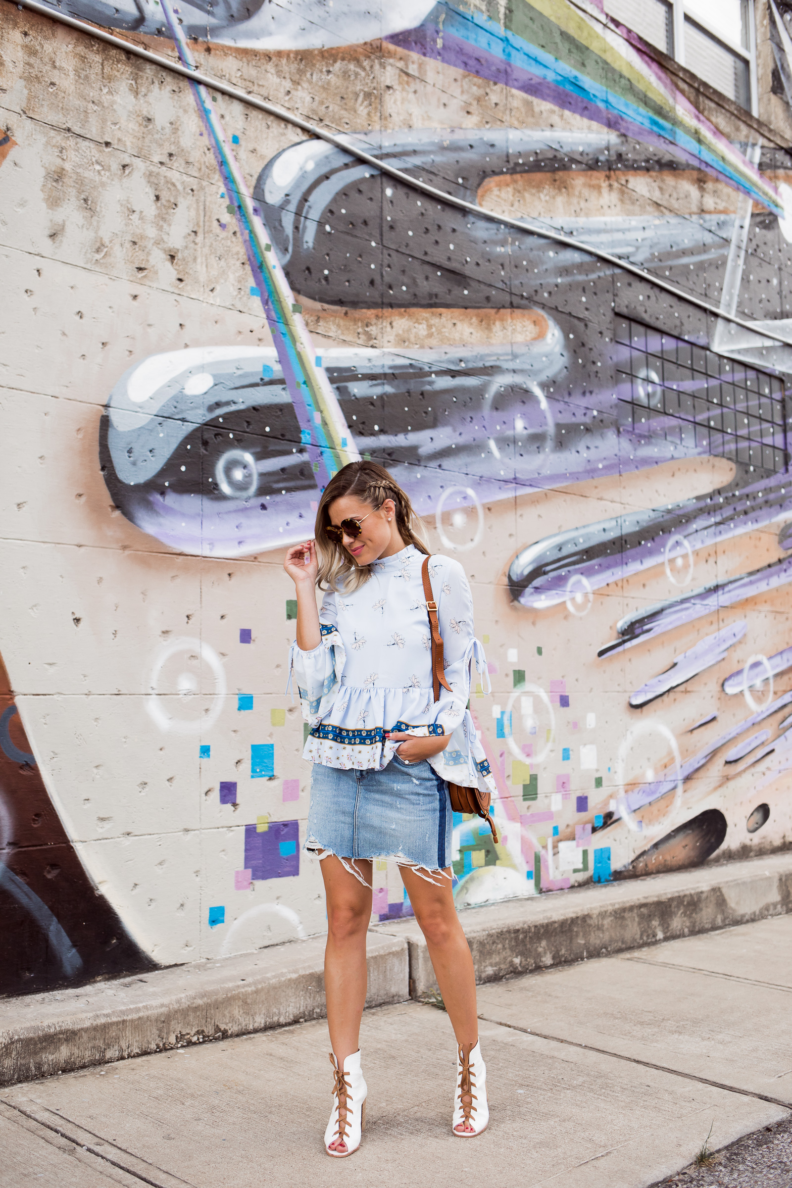 Houston fashion blogger Uptown with Elly Brown wears Kristin Cavallari white boots with a denim skirt.