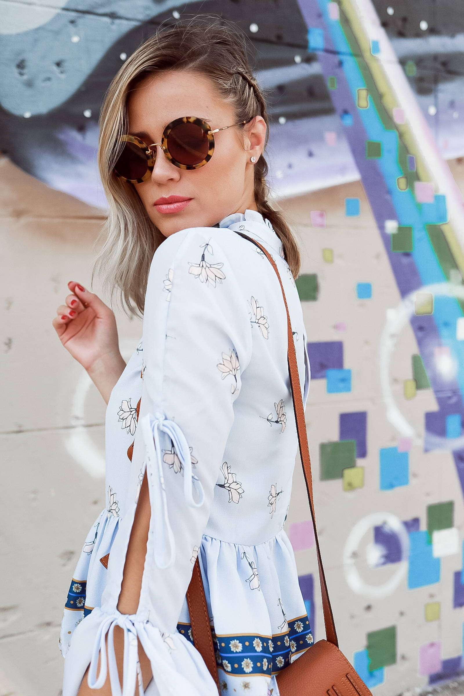 Houston fashion blogger Uptown with Elly Brown wears a floral top and Prada round sunglasses