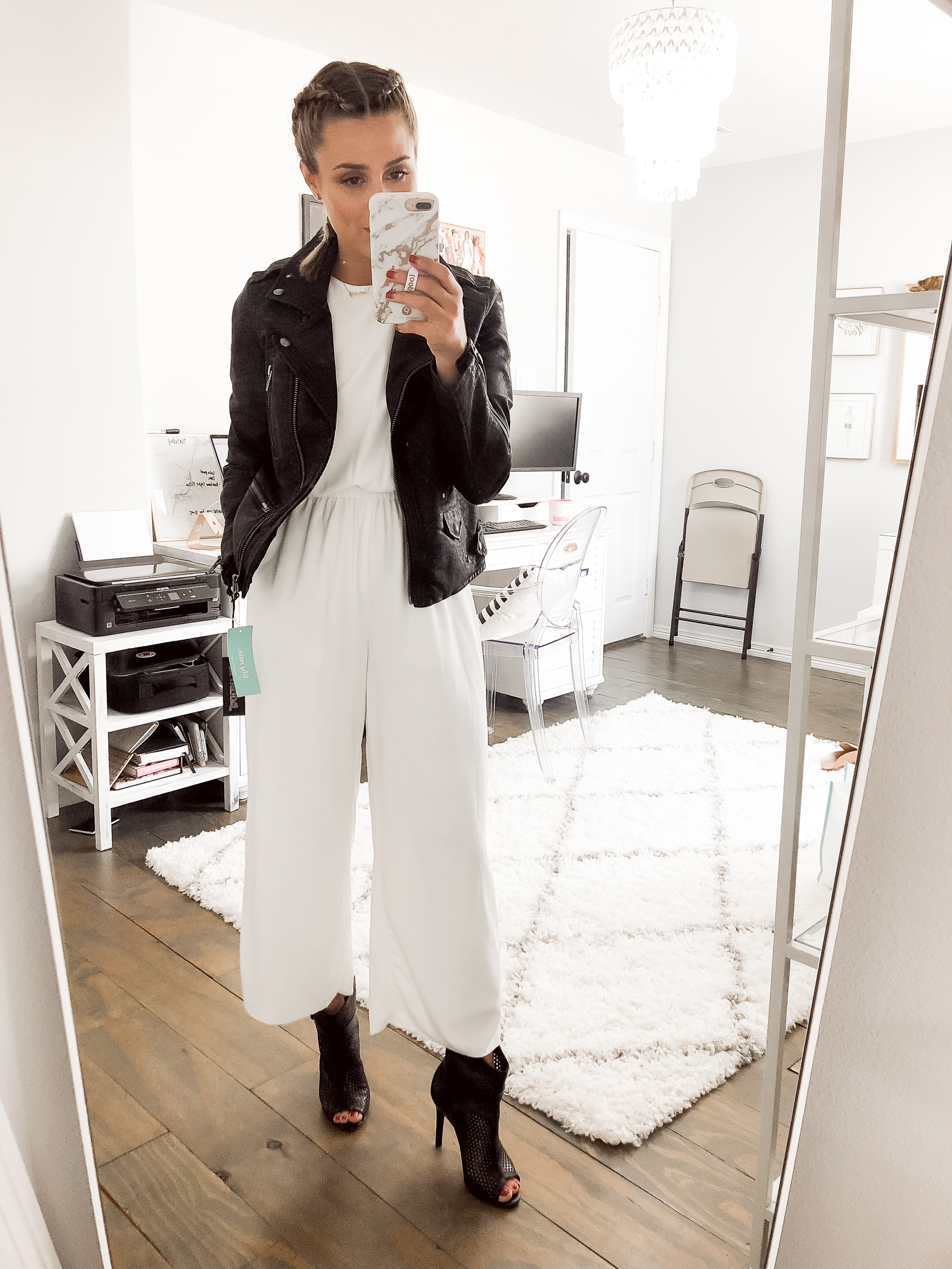 Houston fashion blogger Uptown with Elly Brown wears a white jumpsuit with a leather jacket