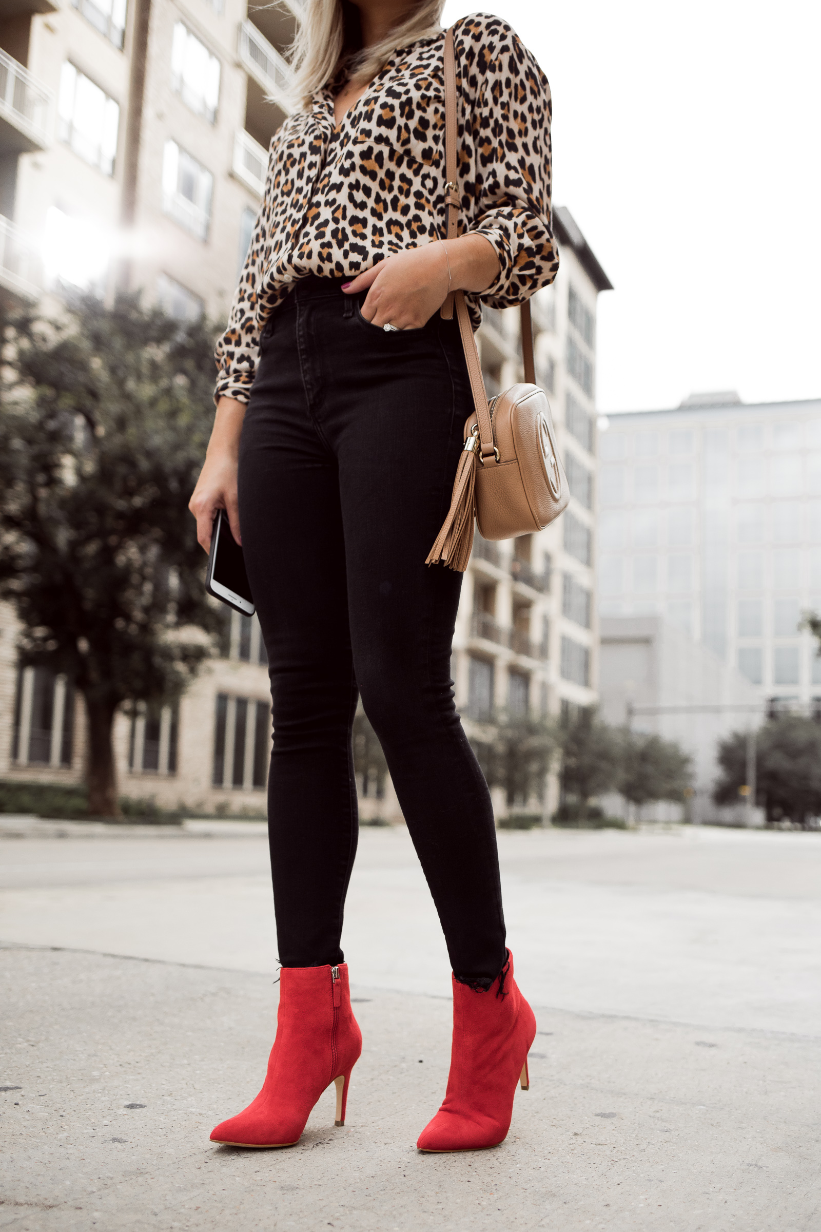 Houston fashion blogger Uptown with Elly Brown wears red ankle boots with a black skinny denim