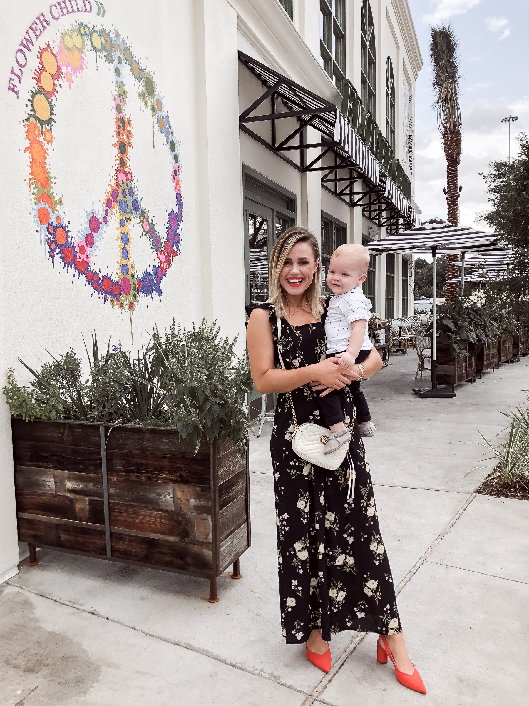 Houston fashion blogger Uptown with Elly Brown wears a floral jumpsuit with bow slingbacks
