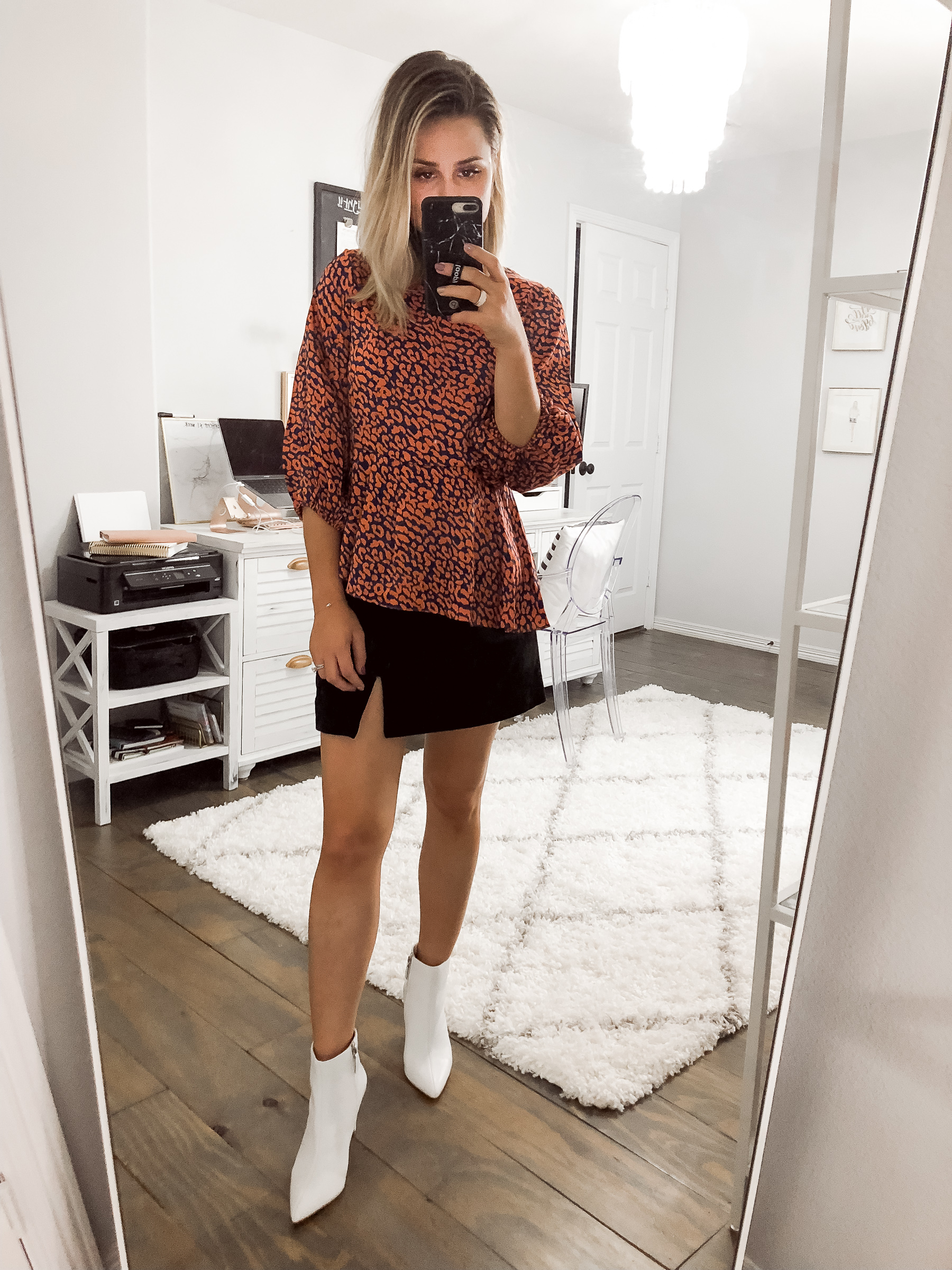 Houston fashion blogger Uptown with Elly Brown wears an animal print top and white ankle boots
