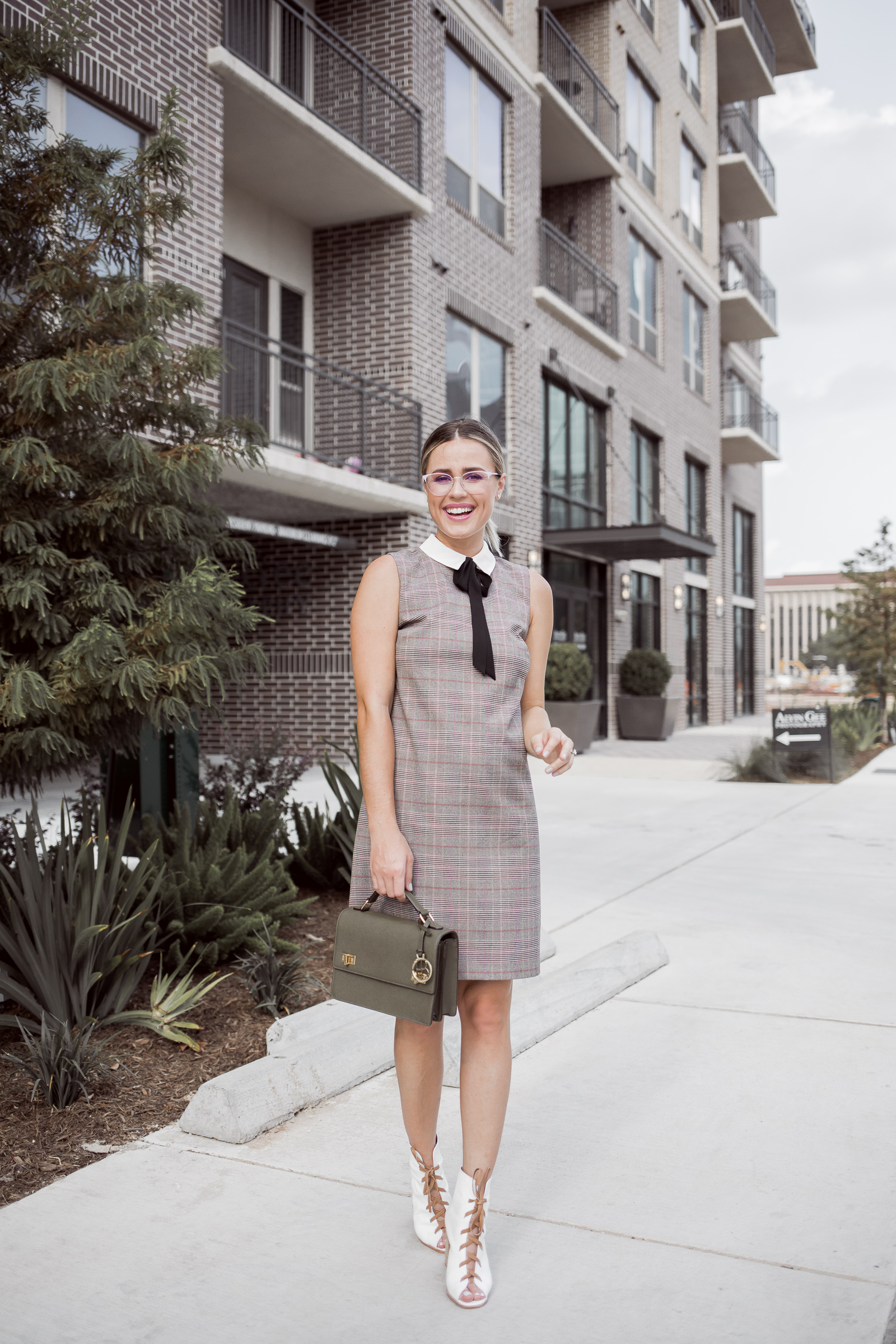 Houston Fashion blogger Uptown with Elly Brown shares how to wear a Plaid Shift Dress paired with white boots for the fall season.