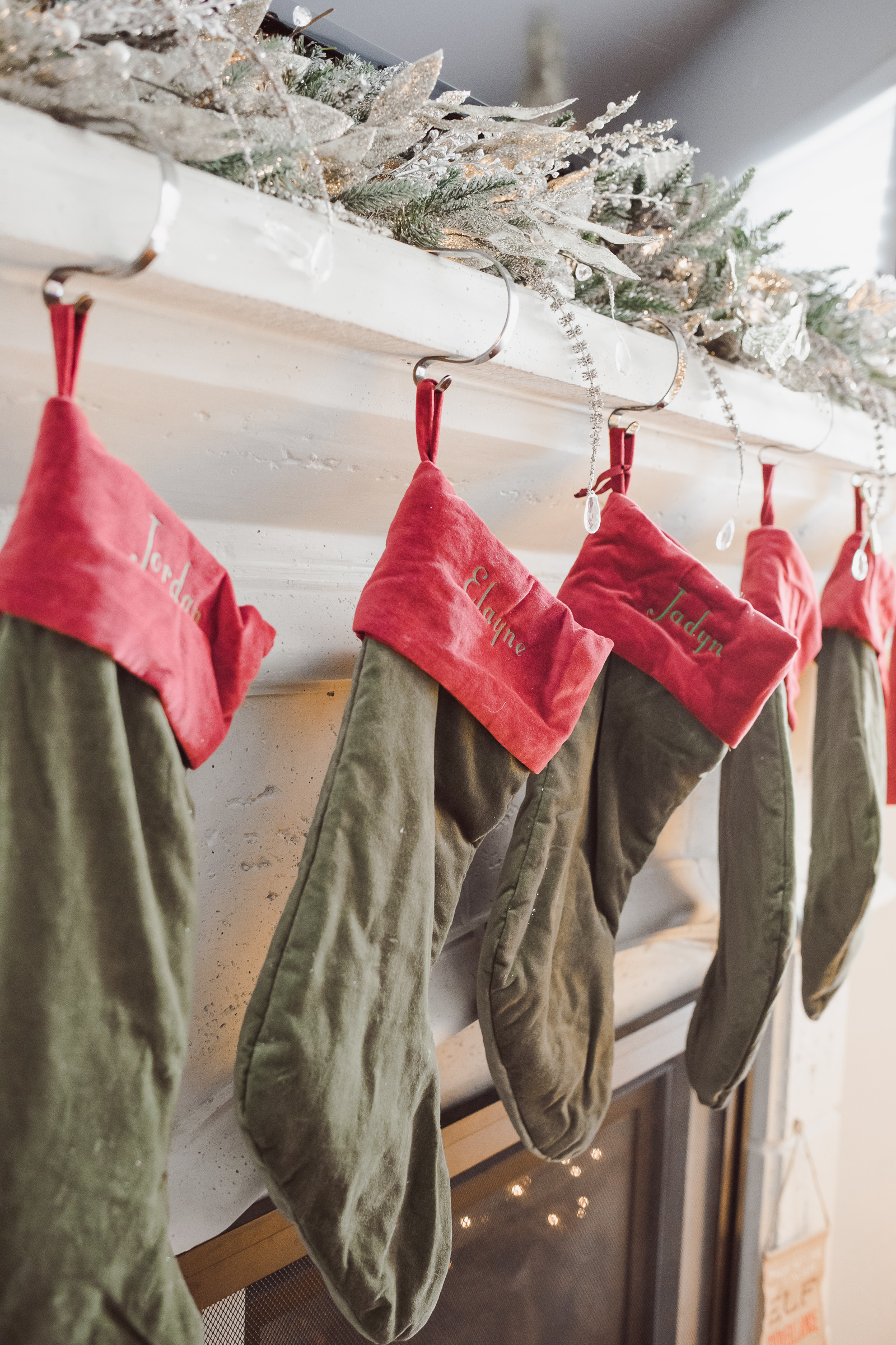 Houston lifestyle blogger Uptown with Elly Brown shares her Pottery Barn Velvet Christmas stockings above her fireplace