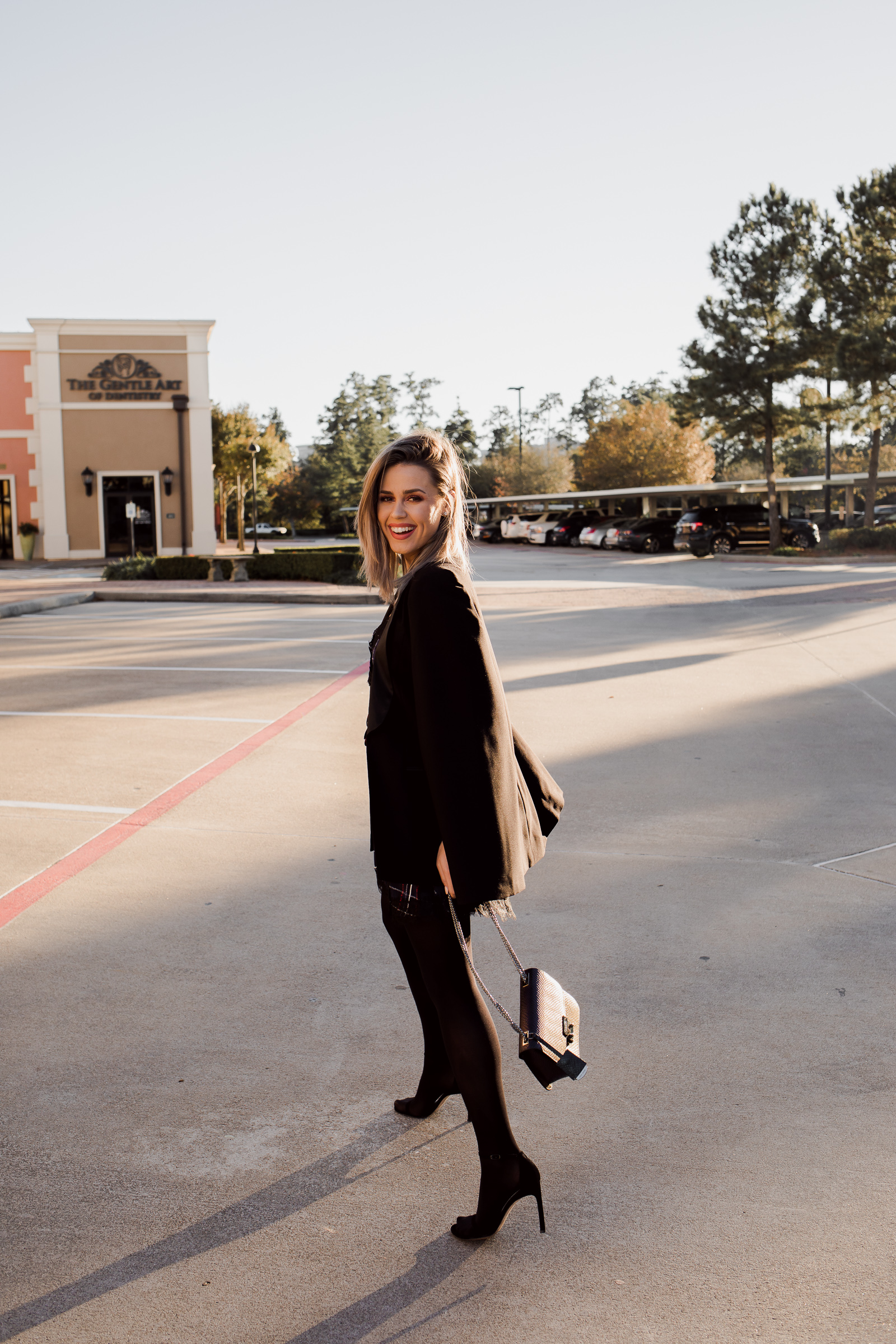 Houston fashion blogger Uptown with Elly Brown wears a tuxedo cap with her plaid dress for the holidays