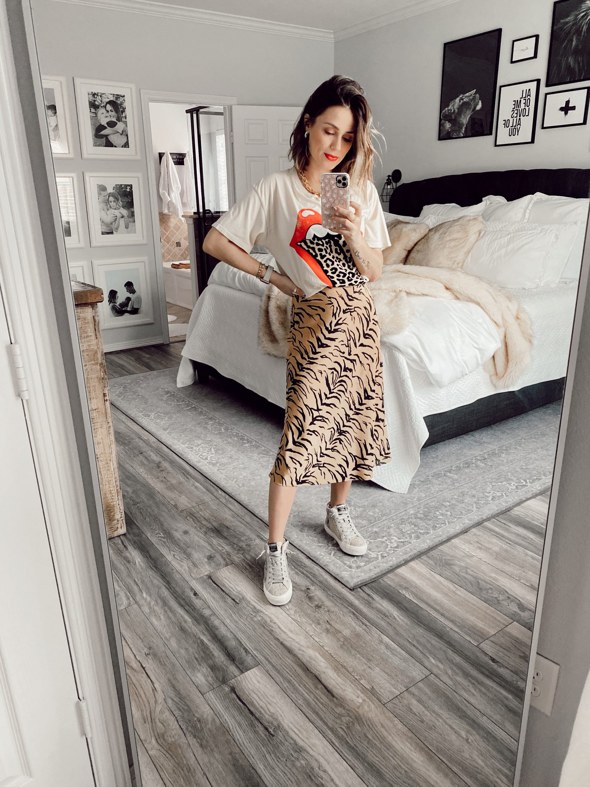 Houston fashion blogger Elly brown wears a Madewell Midi skirt paired with a graphic leopard tee