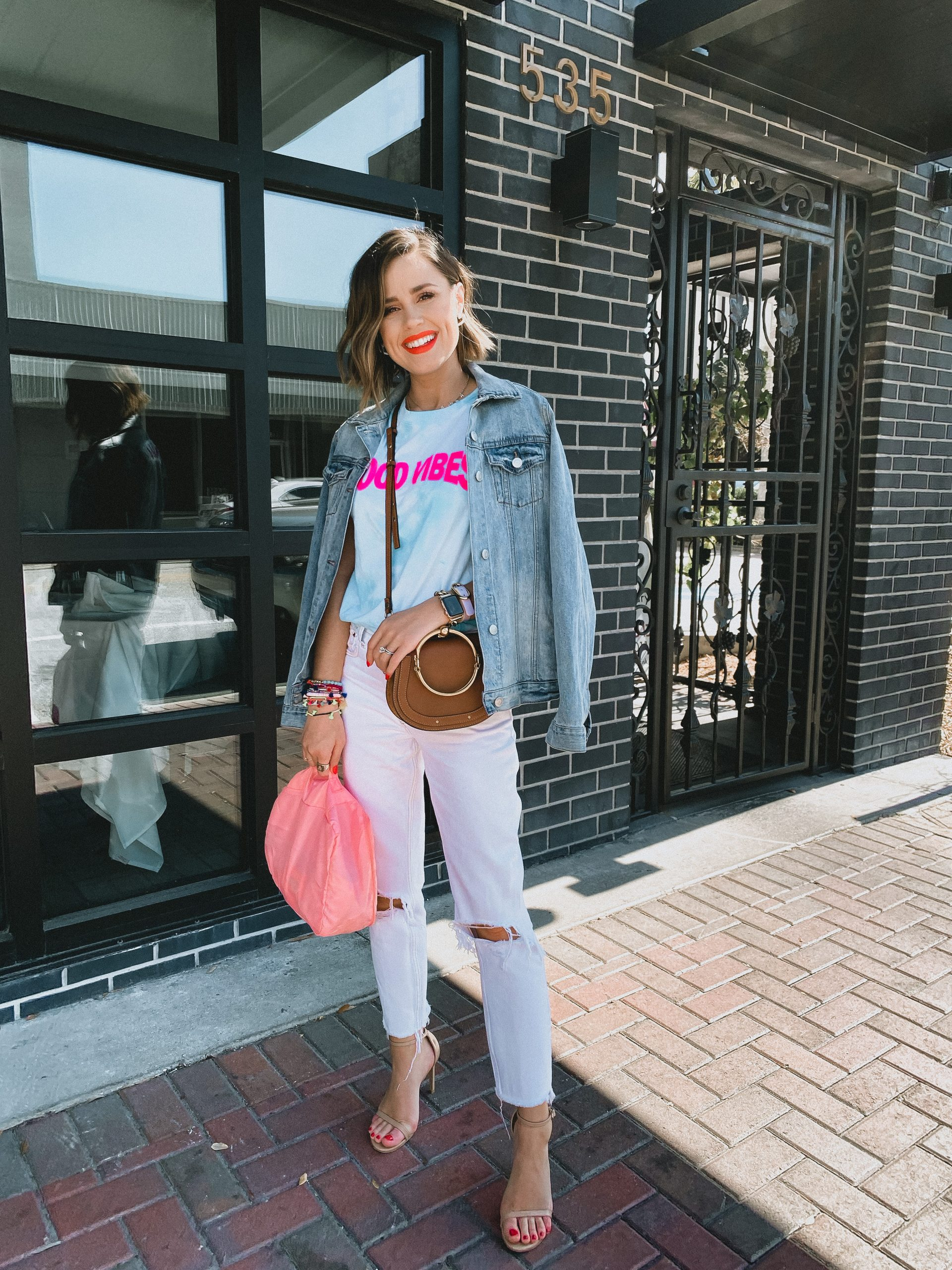 Houston fashion blogger Elly brown wears a tie-dye graphic tee with distressed mom jeans
