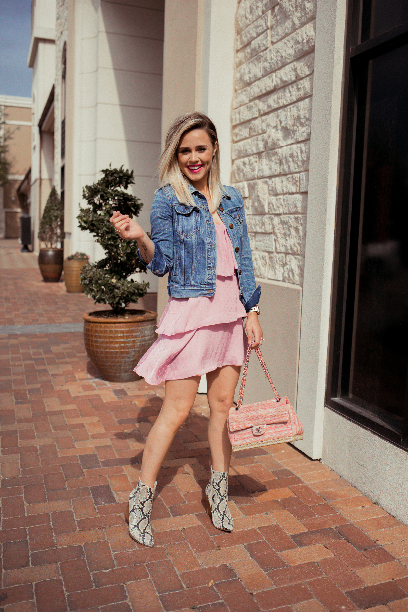 Houston fashion blogger Elly Brown wears a pink ruffle dress with a denim jacket for a western outfit