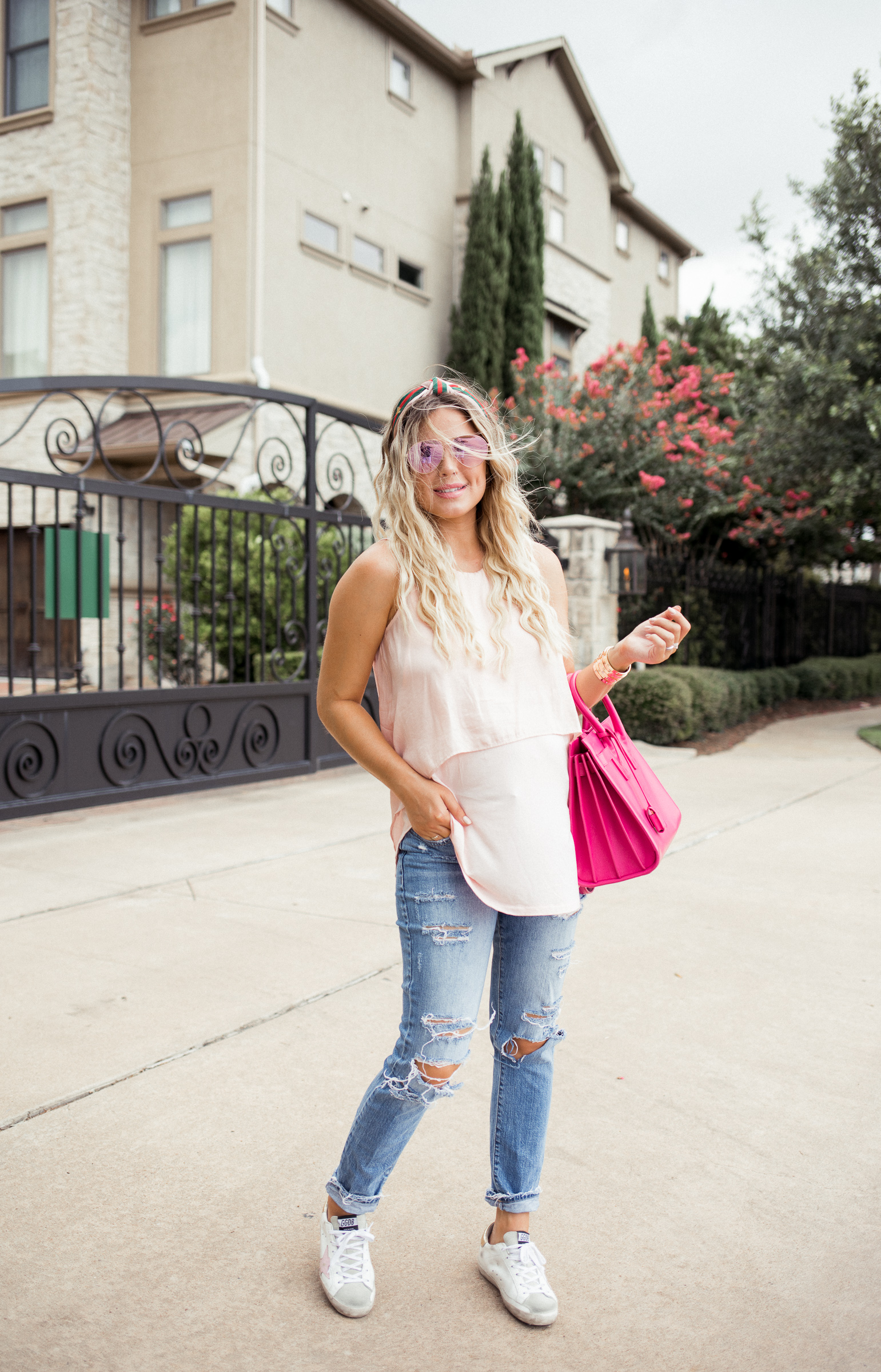 Houston blogger Uptown with Elly Brown wears golden goose sneakers with a pink top and distressed denim