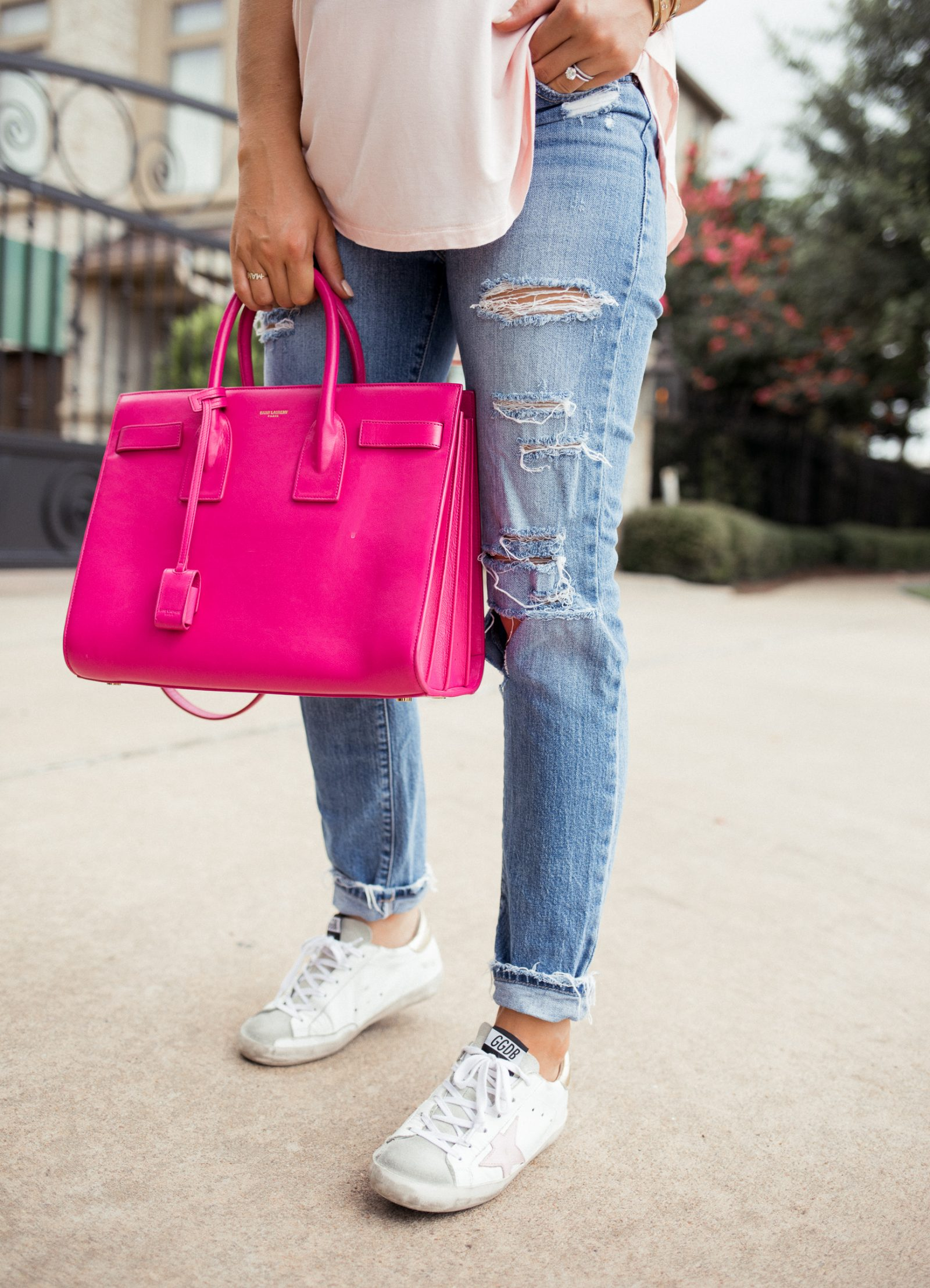 Houston blogger Uptown with Elly Brown wears golden goose sneakers with distressed denim and a YSL Sac de Jour