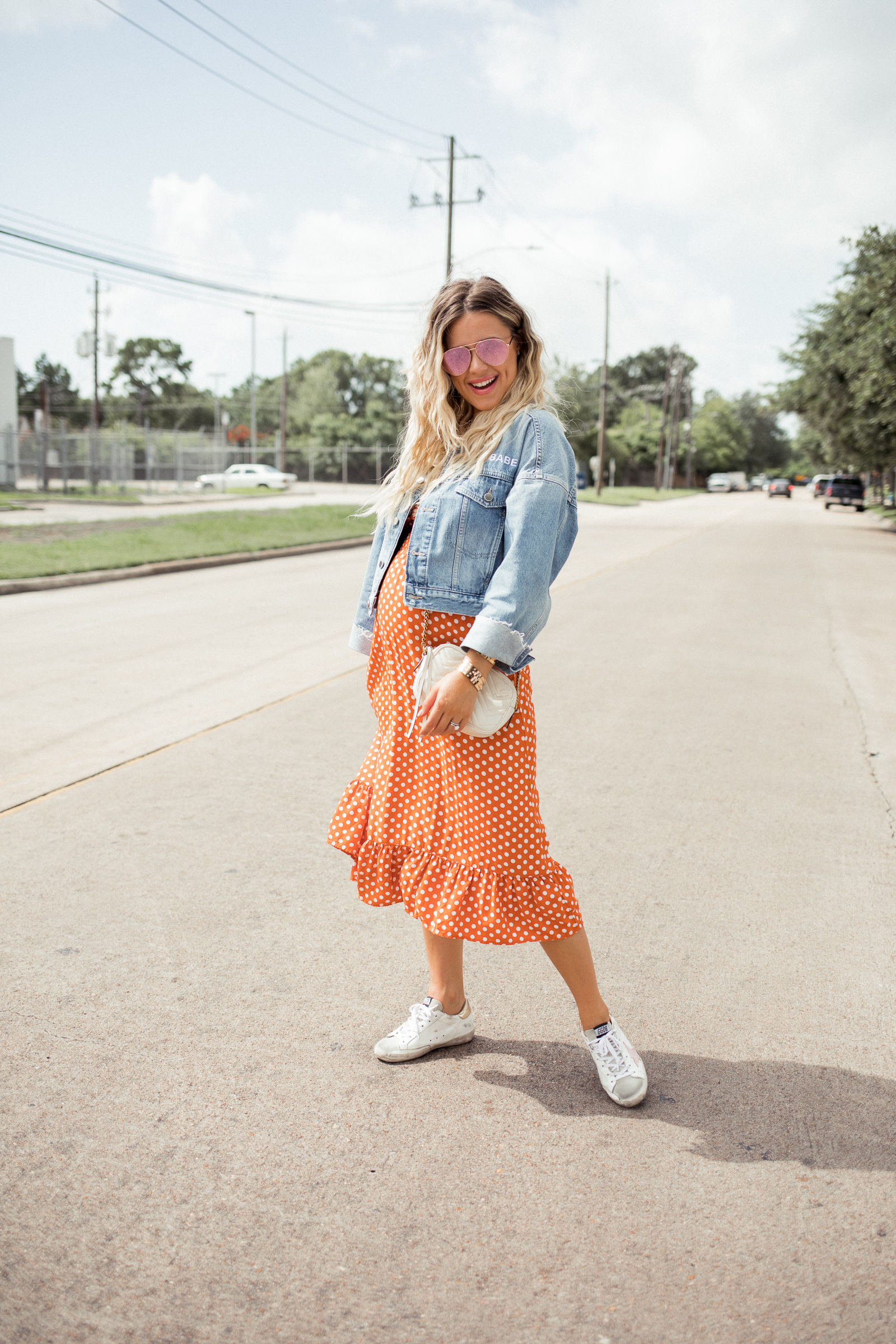 Houston blogger Uptown with Elly Brown wears golden goose sneakers with a ruffle polka dot dress and a denim jacket