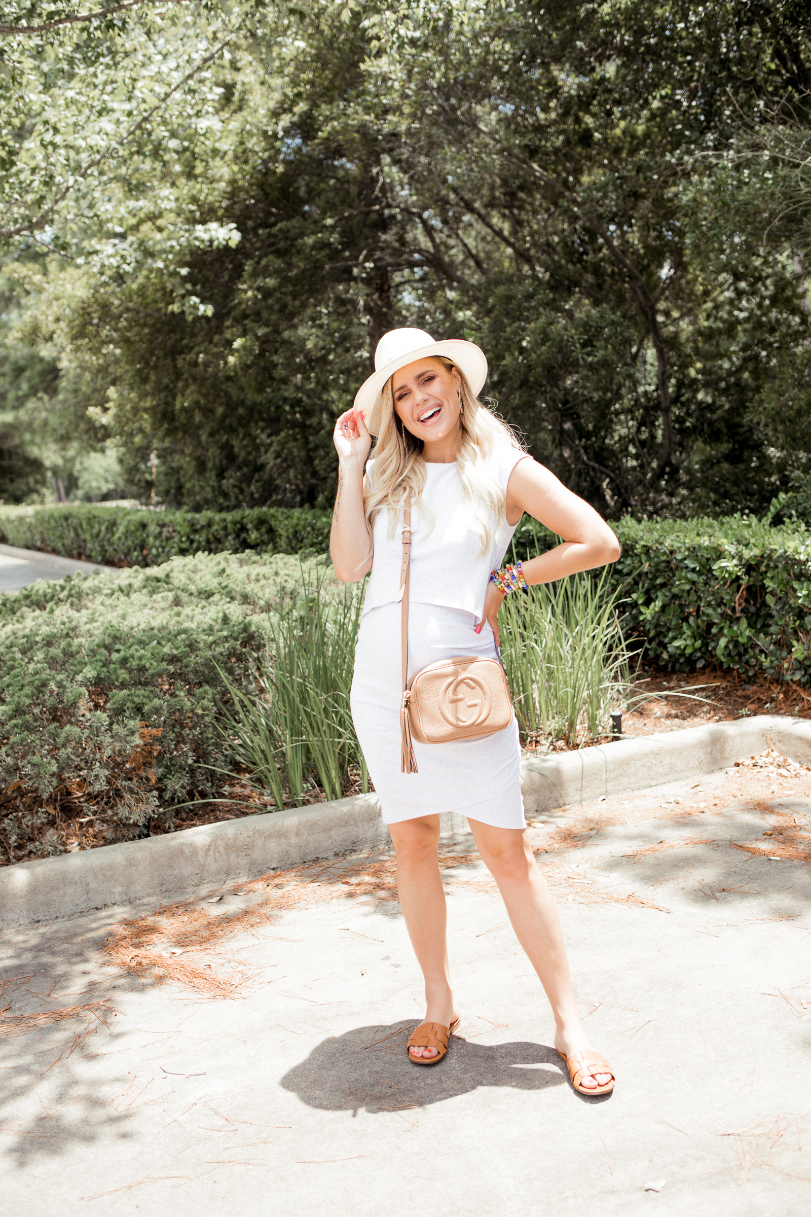 Houston fashion blogger wears a body-con maternity dress with sandals and a straw summer hat