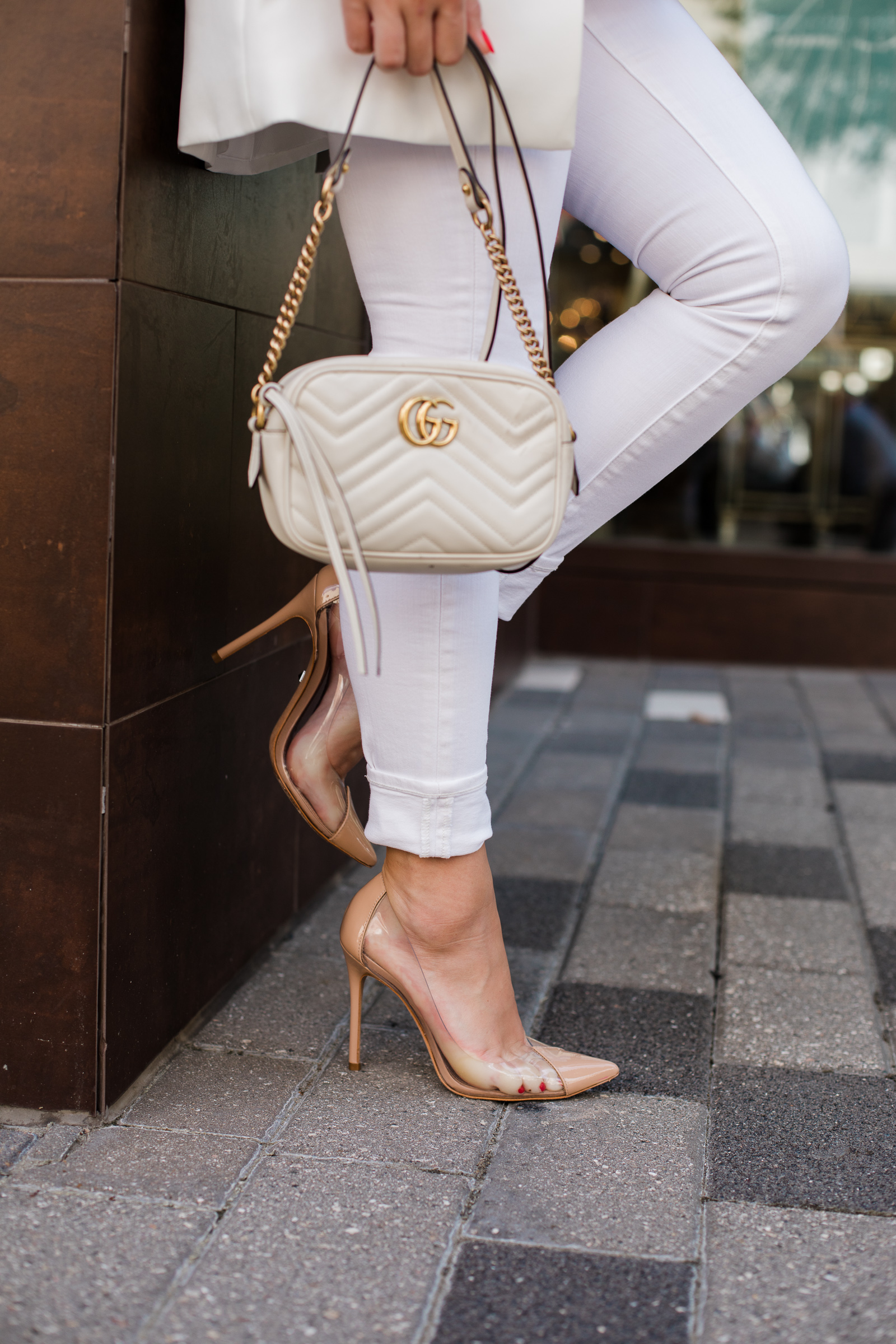 Houston fashion blogger Elly Brown wears white skinny jeans cuffed see through heels from Schutz