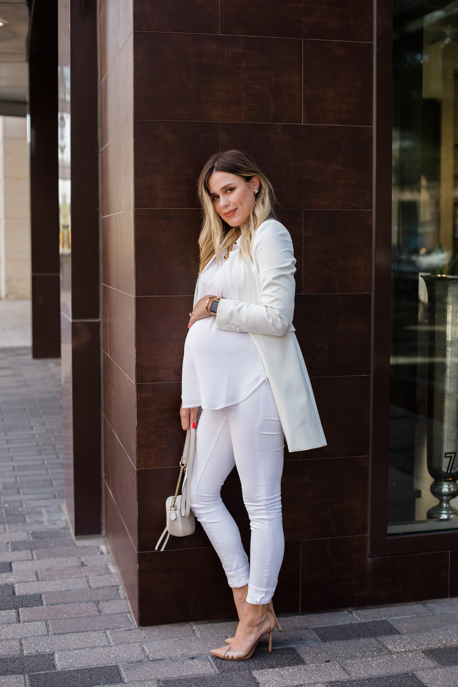 Houston fashion blogger Elly Brown wears an all white outfit with see through heel pumps from Schutz