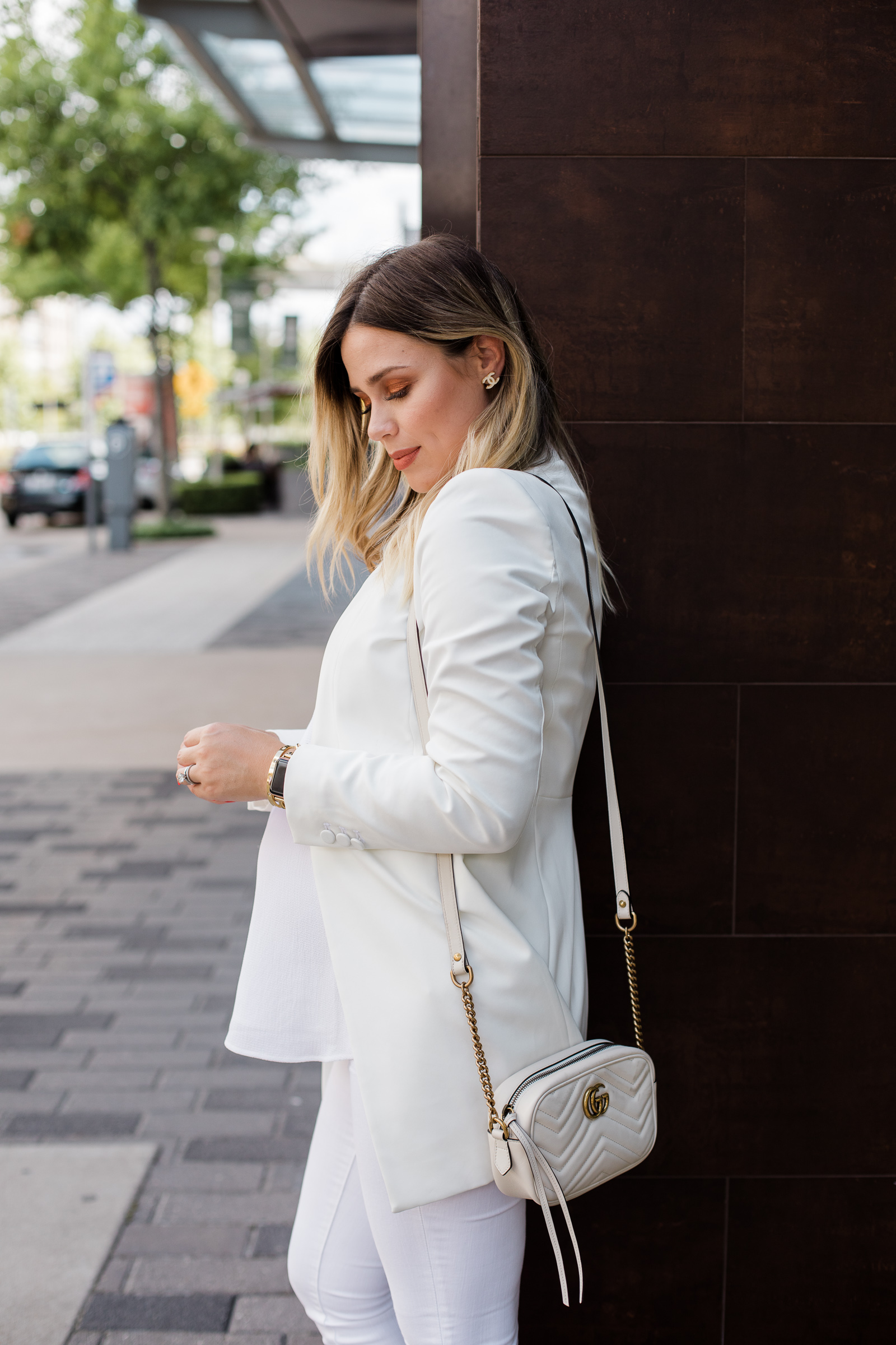 Houston fashion blogger Elly Brown wears a white blazer with a Gucci bag