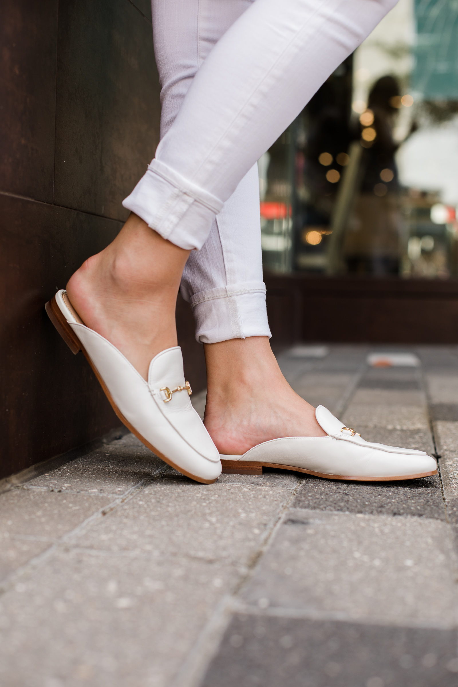 Houston fashion blogger Elly Brown wears white skinny jeans cuffed with while Sam Edelman flat mules