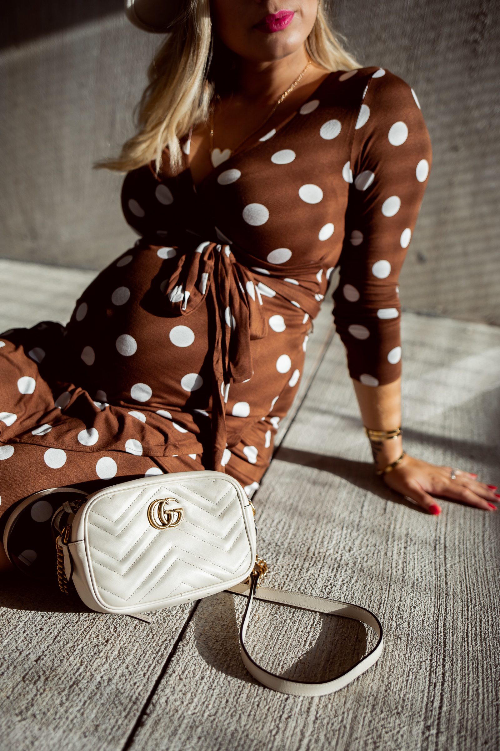 houston fashion blogger Elly Brown wears a maternity polka dot dress from HM along with her Gucci bag
