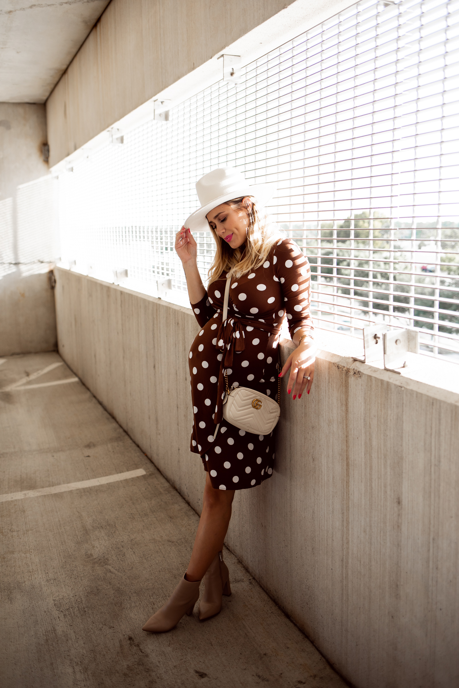 houston fashion blogger Elly Brown wears a maternity polka dot dress with ankle booties and a wool hat