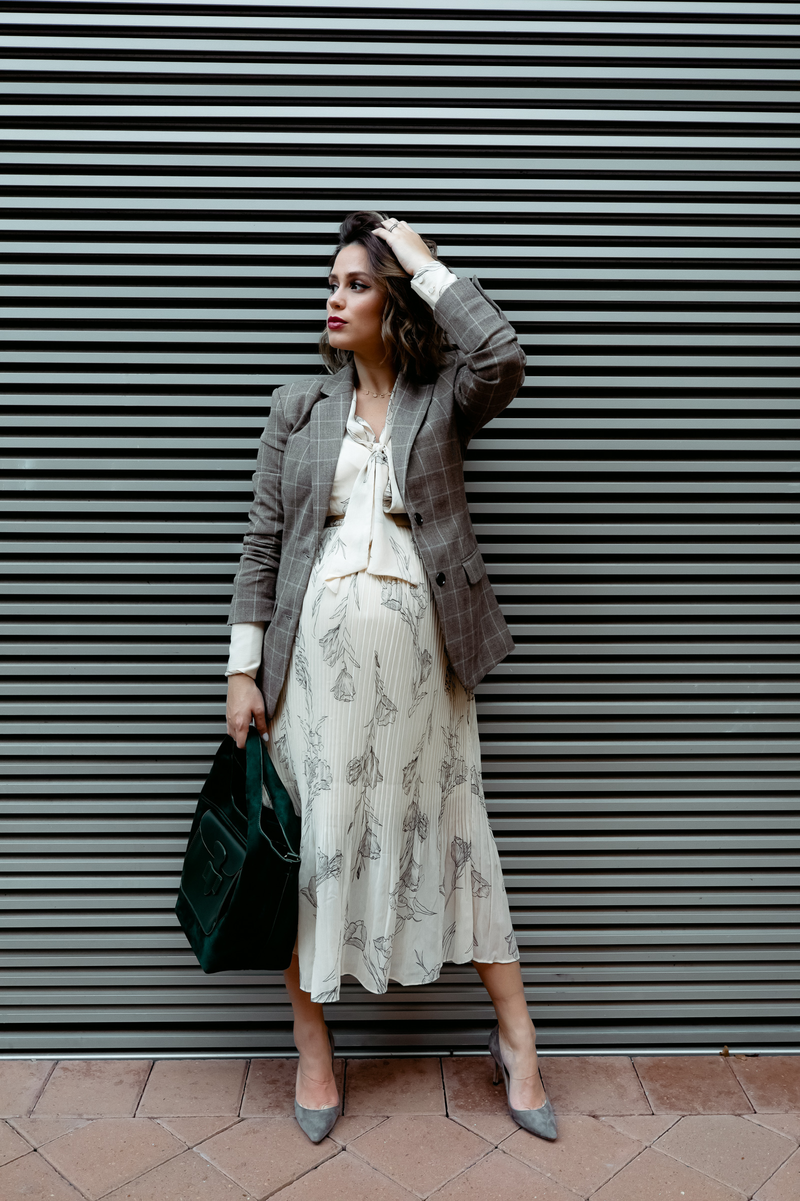 Elly Brown wears a Target pleated fall dress that's under $35 with grey suede heels and a blazer for a chic work outfit