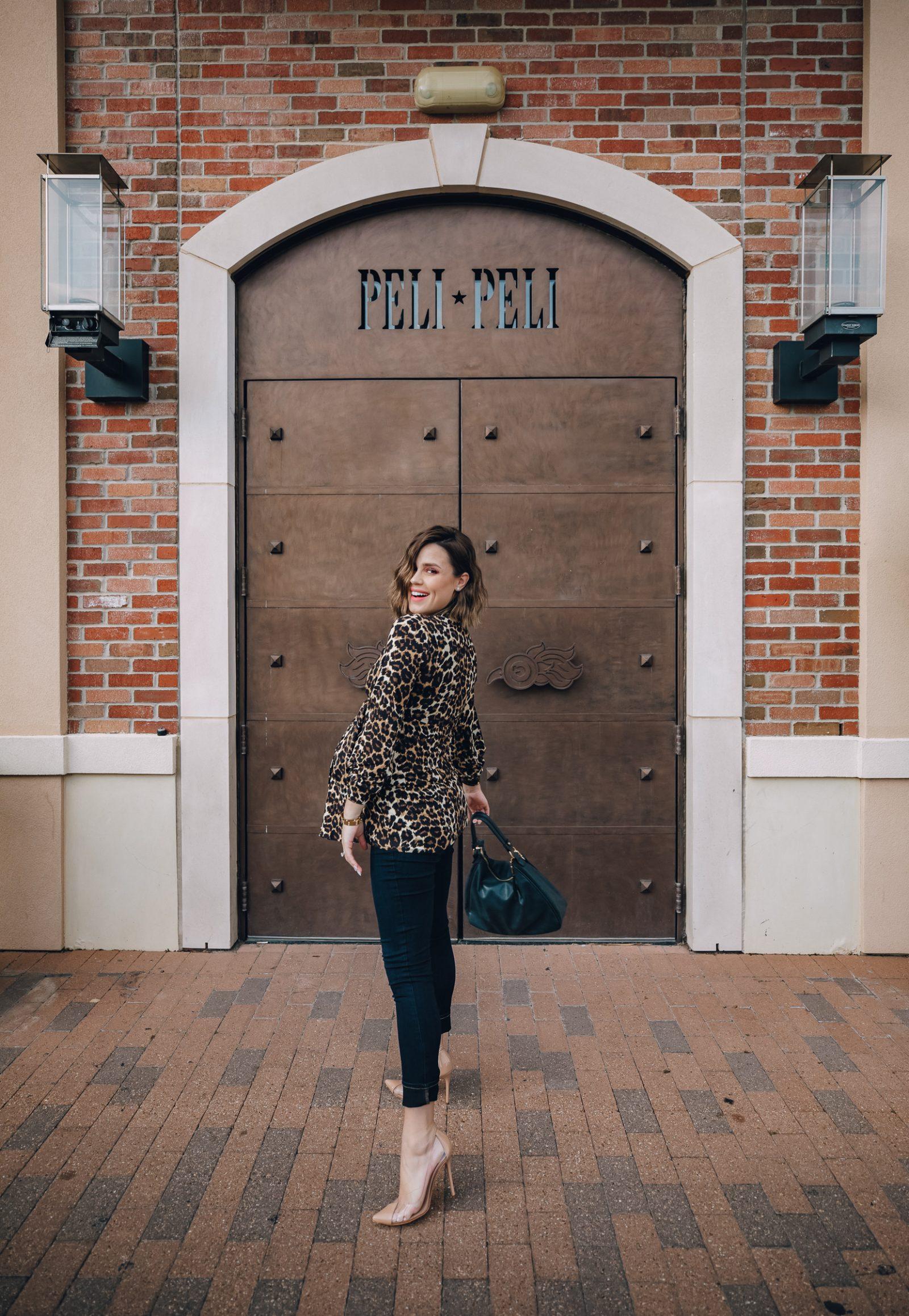 fashion blogger Elly Brown wears a skinny maternity jeans with heels and a leopard top