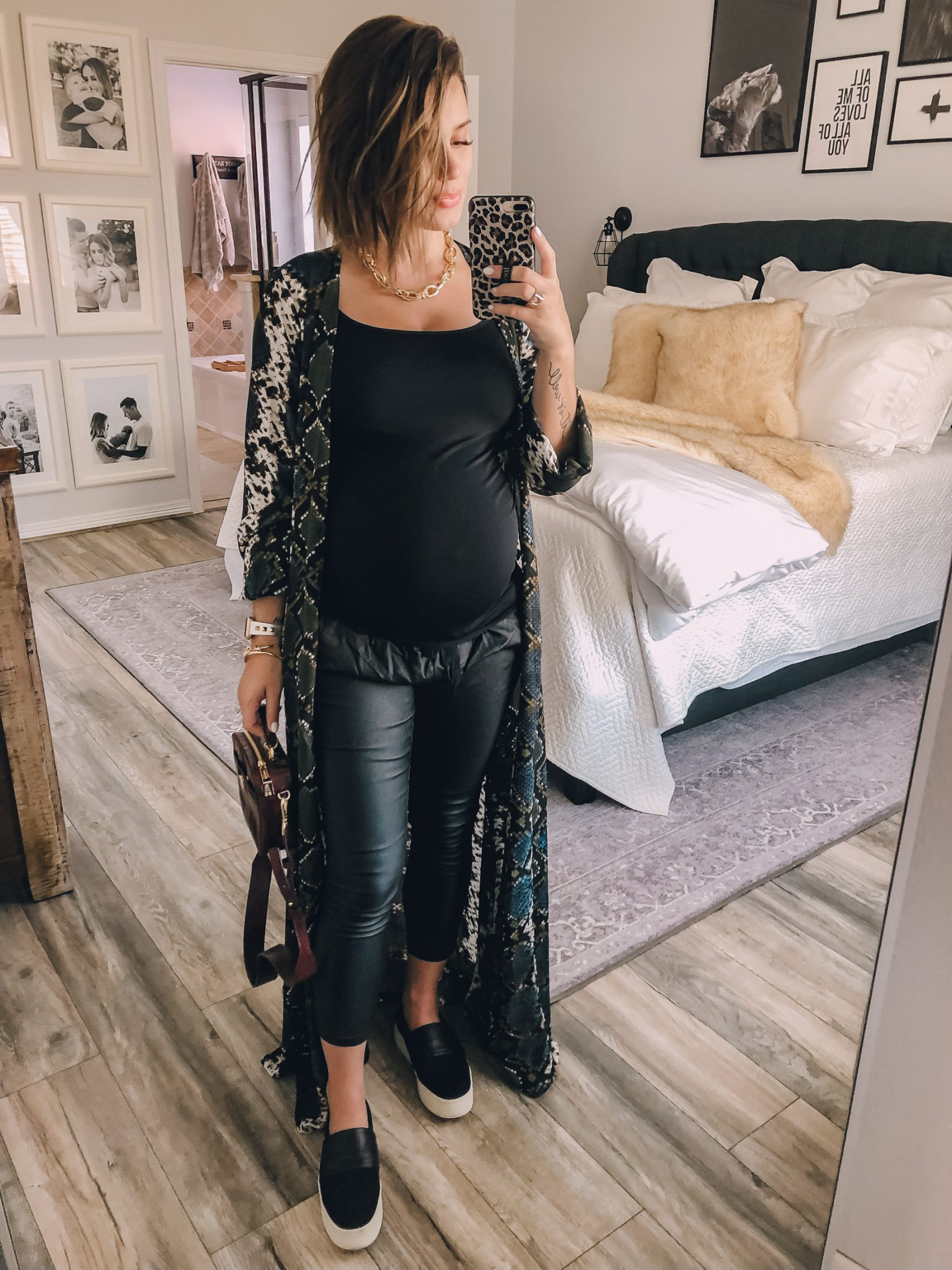 Fashion blogger Elly Brown wears a snake print duster from Buddy Love with faux leather joggers and slip on sneakers