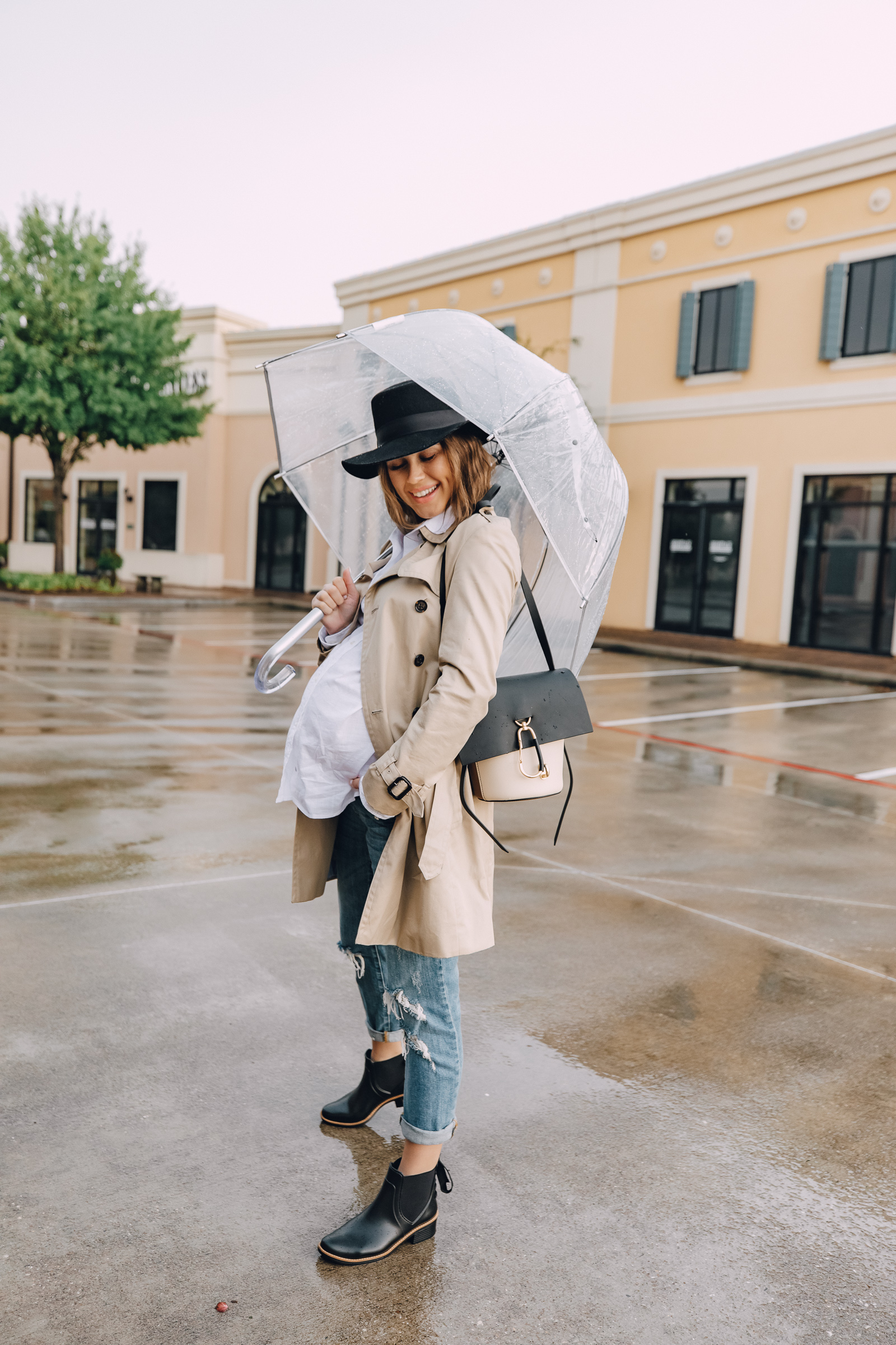 Fashion blogger Elly Brown wears a trench coat paired with a Zac Posen bag and Bernardo rain boots