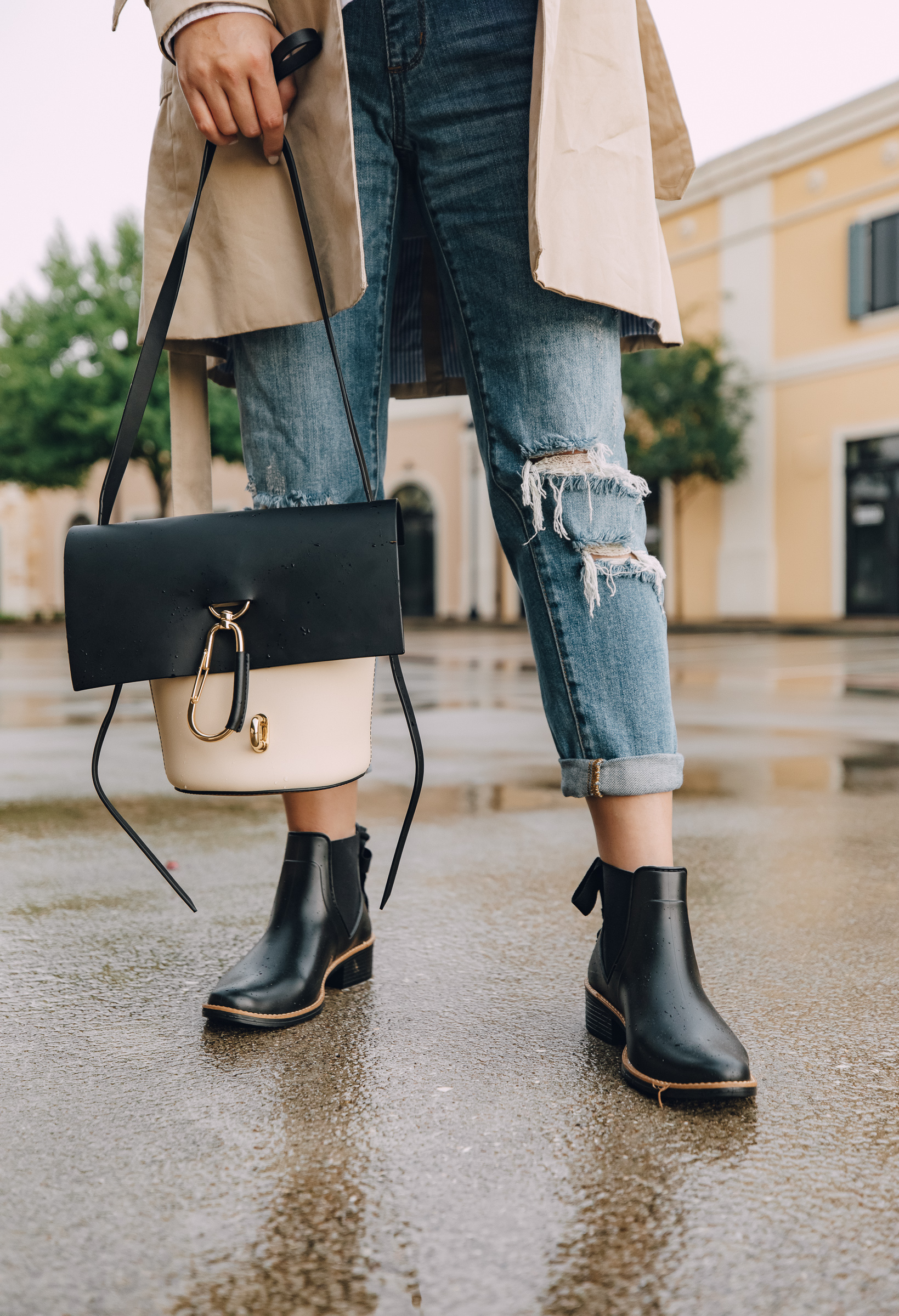 Elly Brown wears a zac posen bag with Bernardo rain boots for a rainy day outfit
