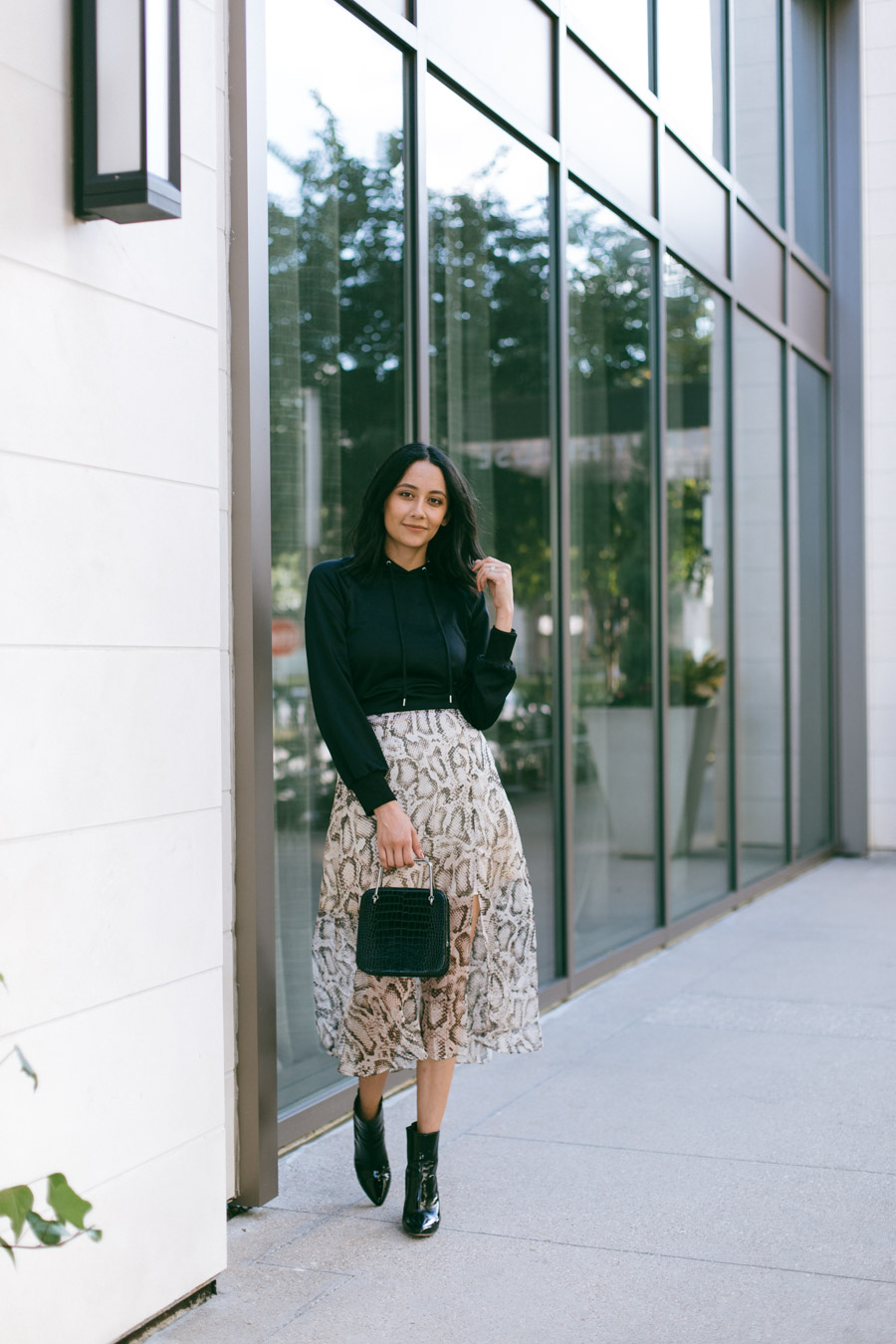 Houston fashion blogger Lilly wears a snake print skirt with black booties and a hoodie sweater