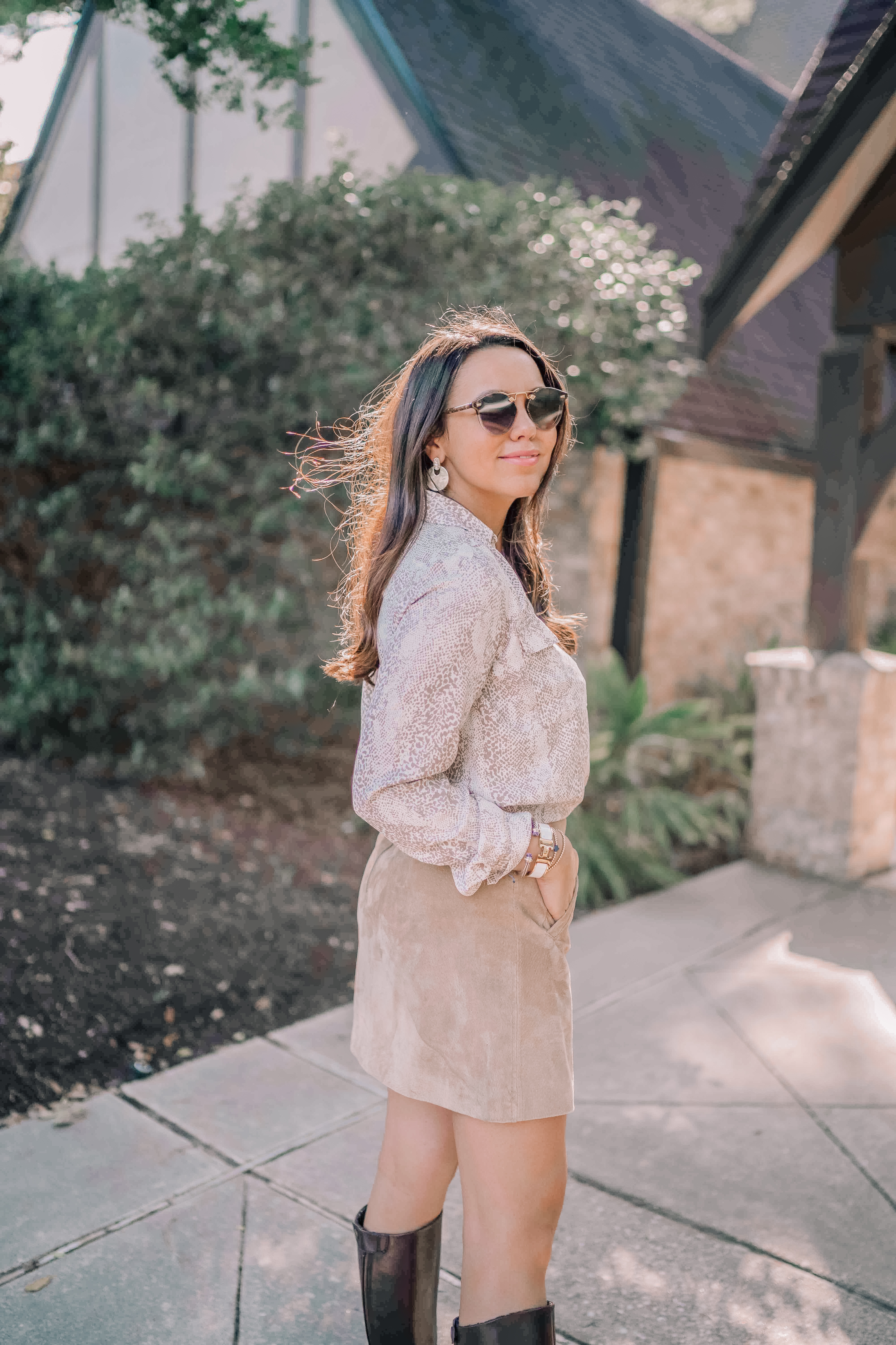 Houston fashion blogger Alex wears a snake print top with a suede skirt and riding boots