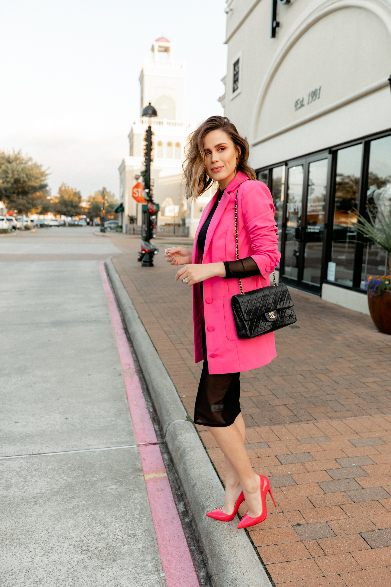 Houston fashion blogger Elly Brown wears a pink blazer with a little black dress and a vintage Chanel