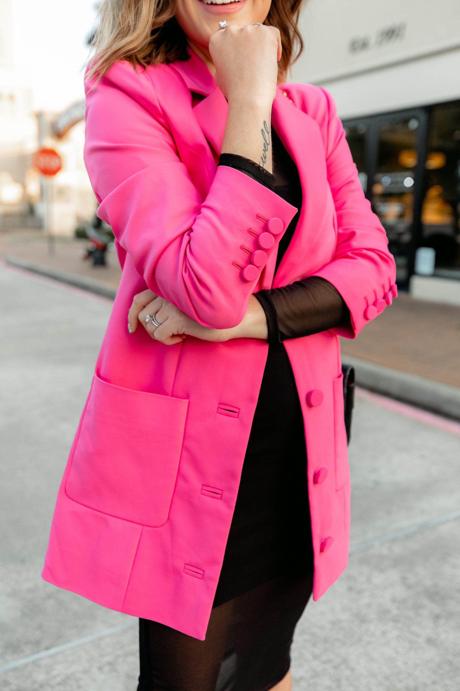 Houston fashion blogger Elly Brown wears an oversized pink blazer paired with a black dress