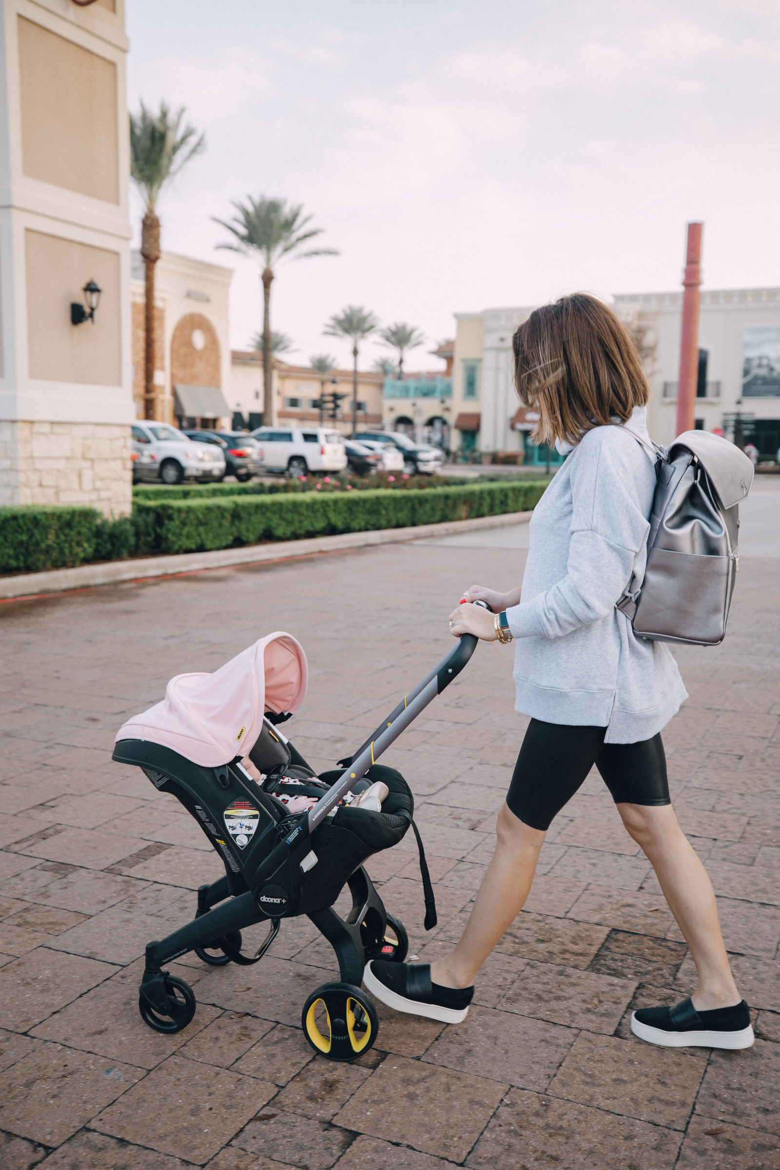 Elly Brown pushes her baby in the doona stroller while wearing faux leather biker shorts with an oversized sweater