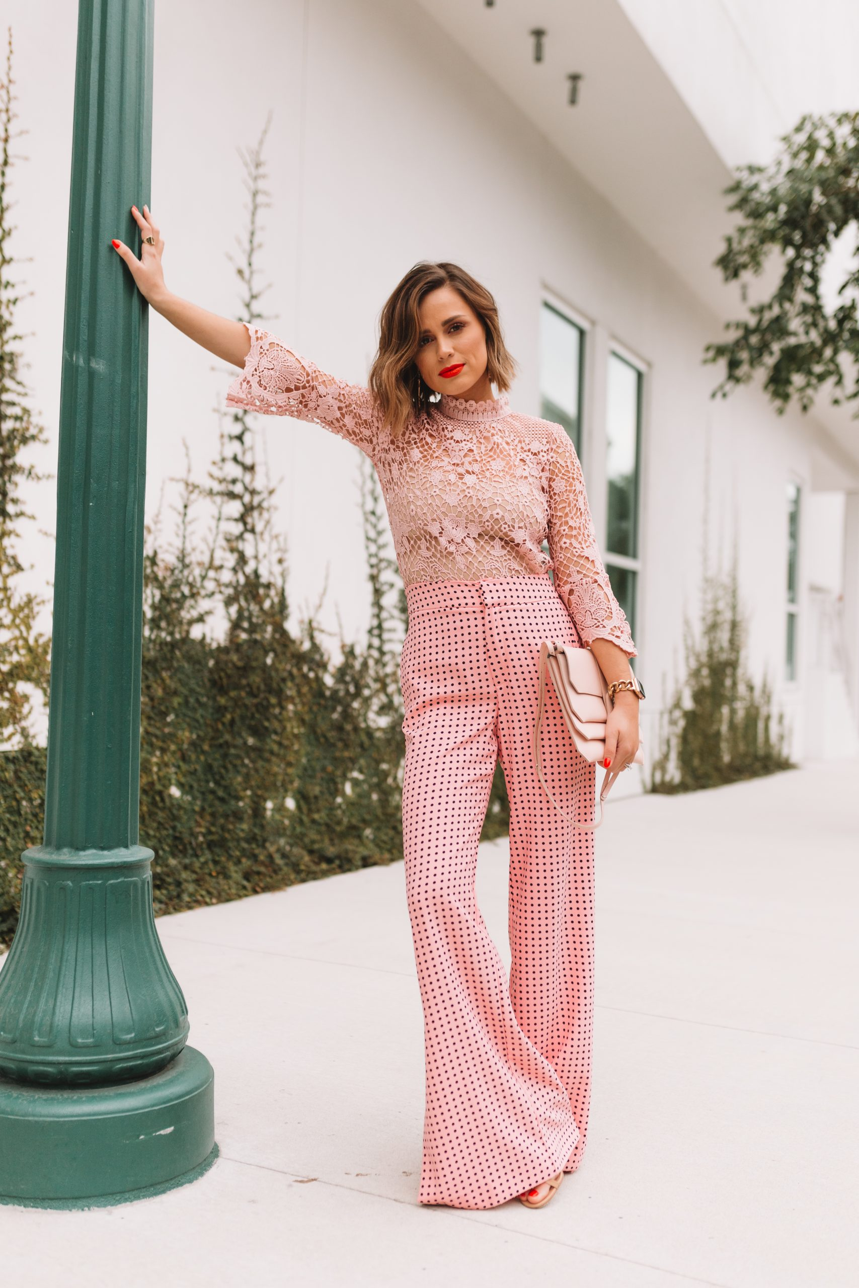 Houston fashion blogger Elly Brown wears a pink lace top and pink polka dot trousers for a feminine outfit