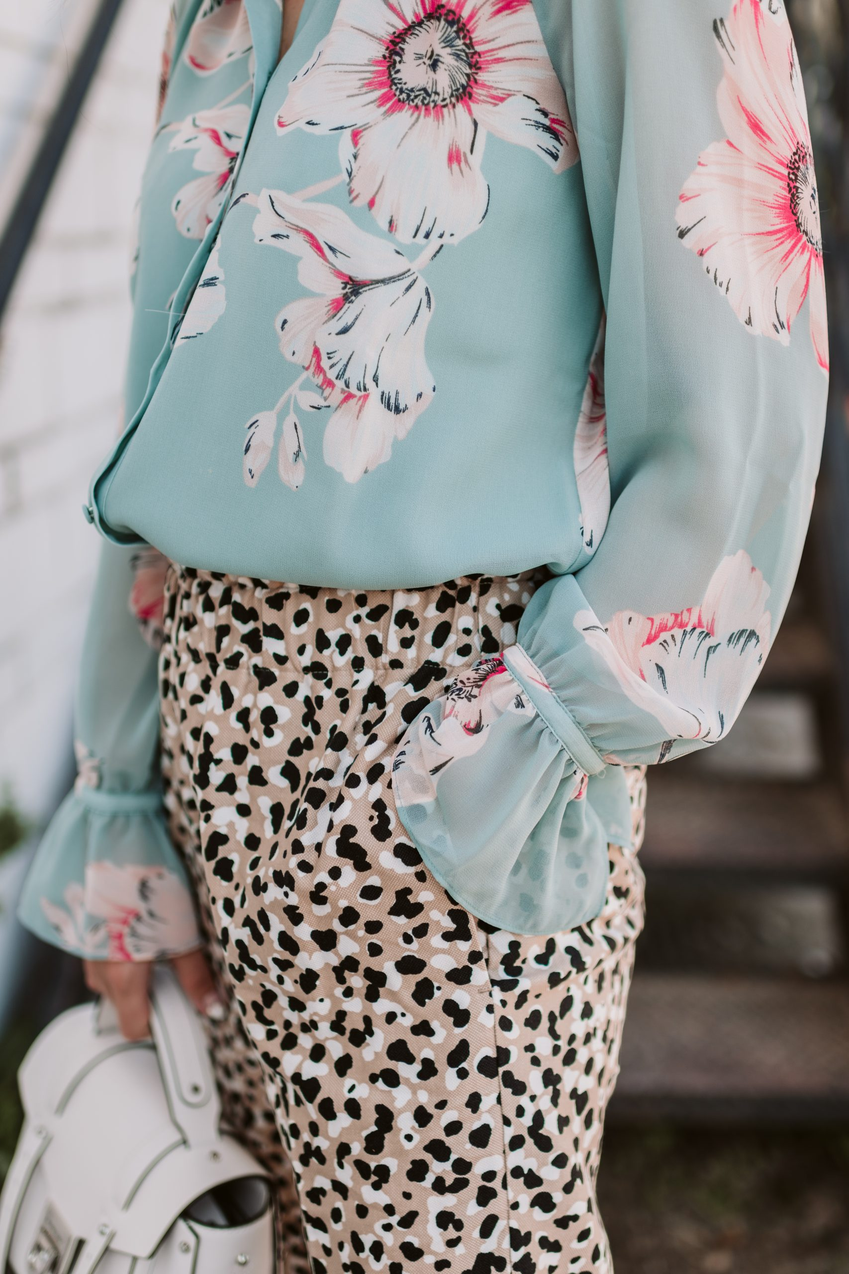 Houston fashion blogger Elly Brown wears a floral top with leopard pants to mix prints