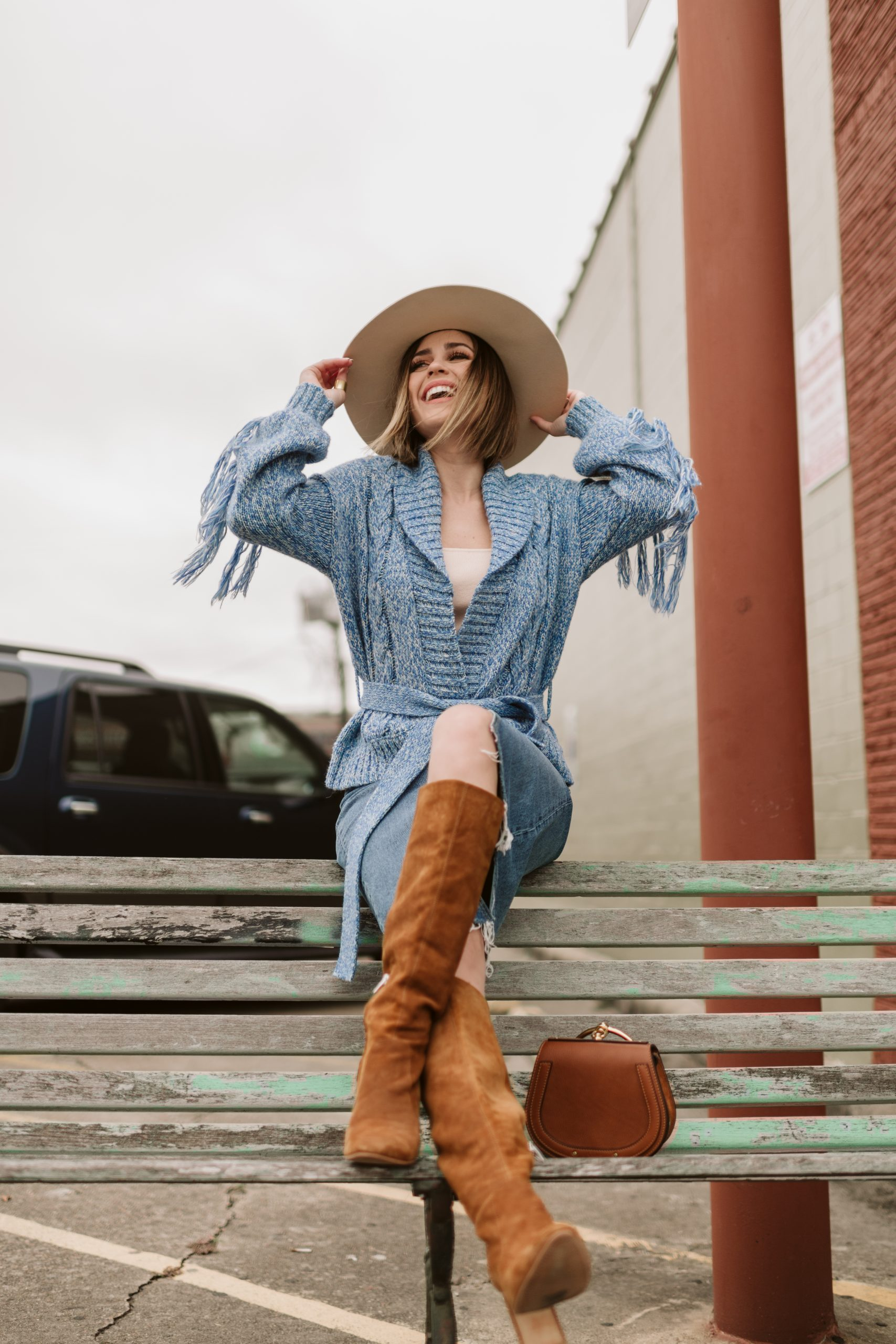 Houston fashion blogger Elly Brown wears a denim skirt with Sam Edelman boots