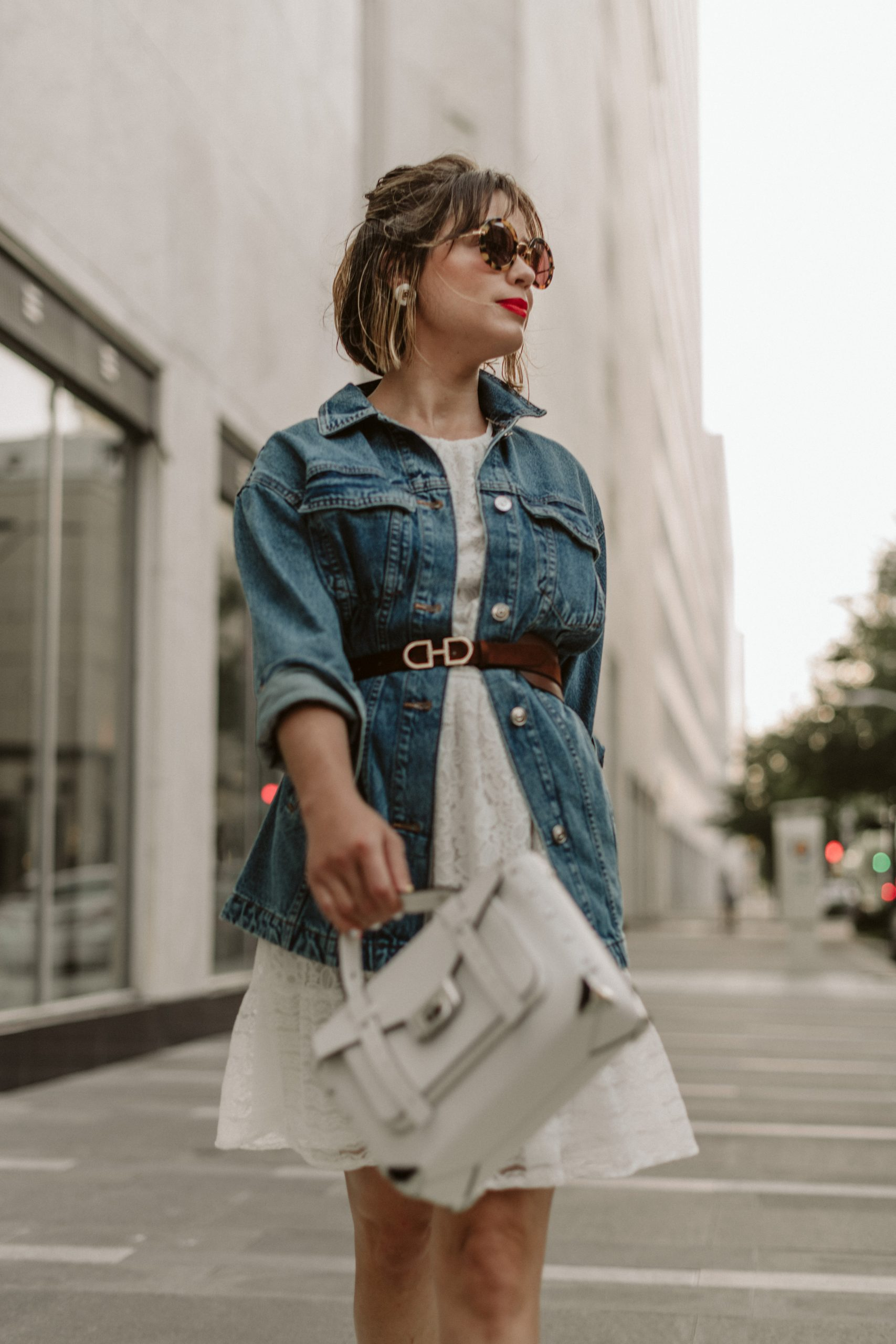 Houston fashion blogger Elly Brown wears a white lace dress with a belted denim jacket