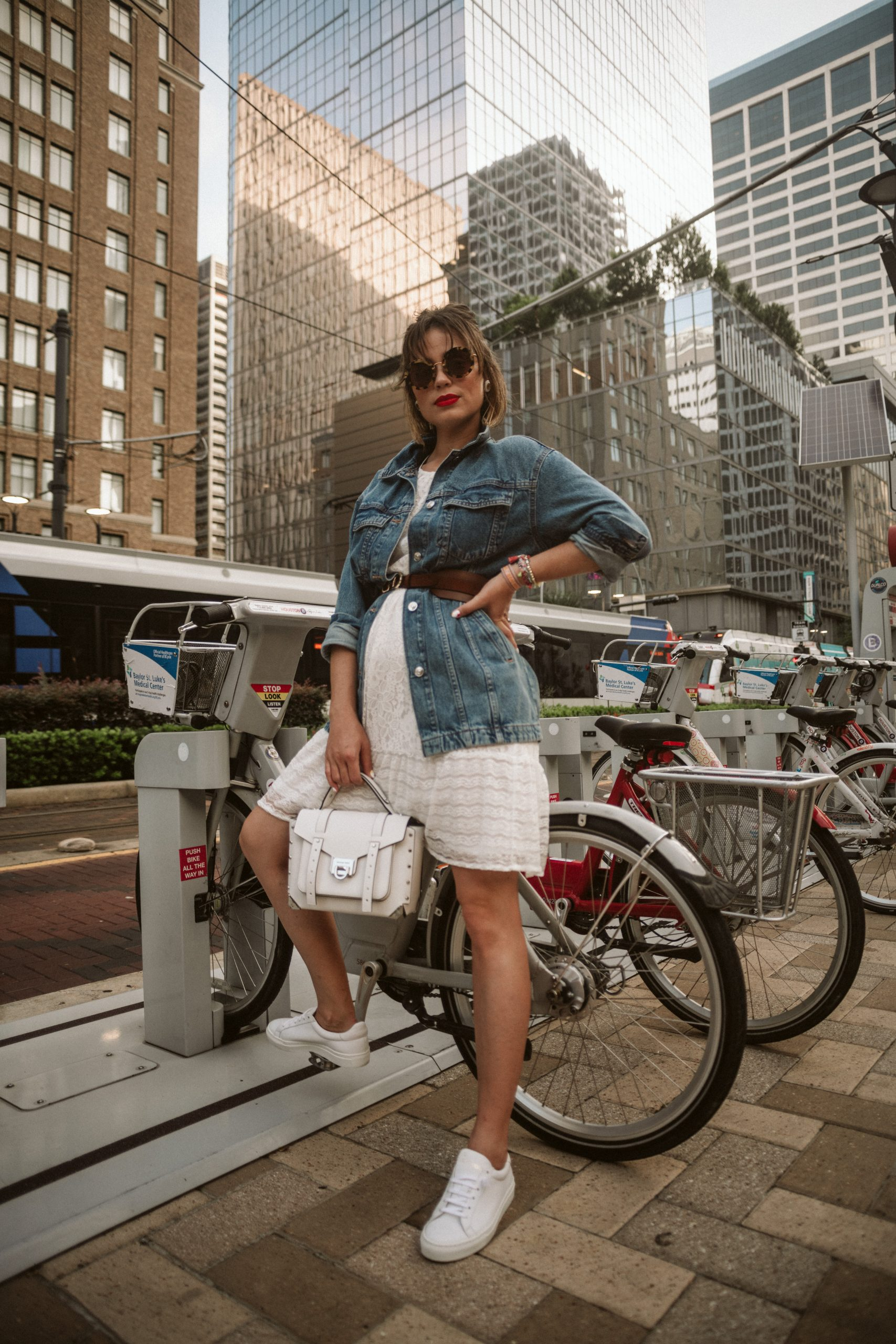 Houston fashion blogger Elly Brown wears a white lace dress with a belted denim jacket and white sneakers