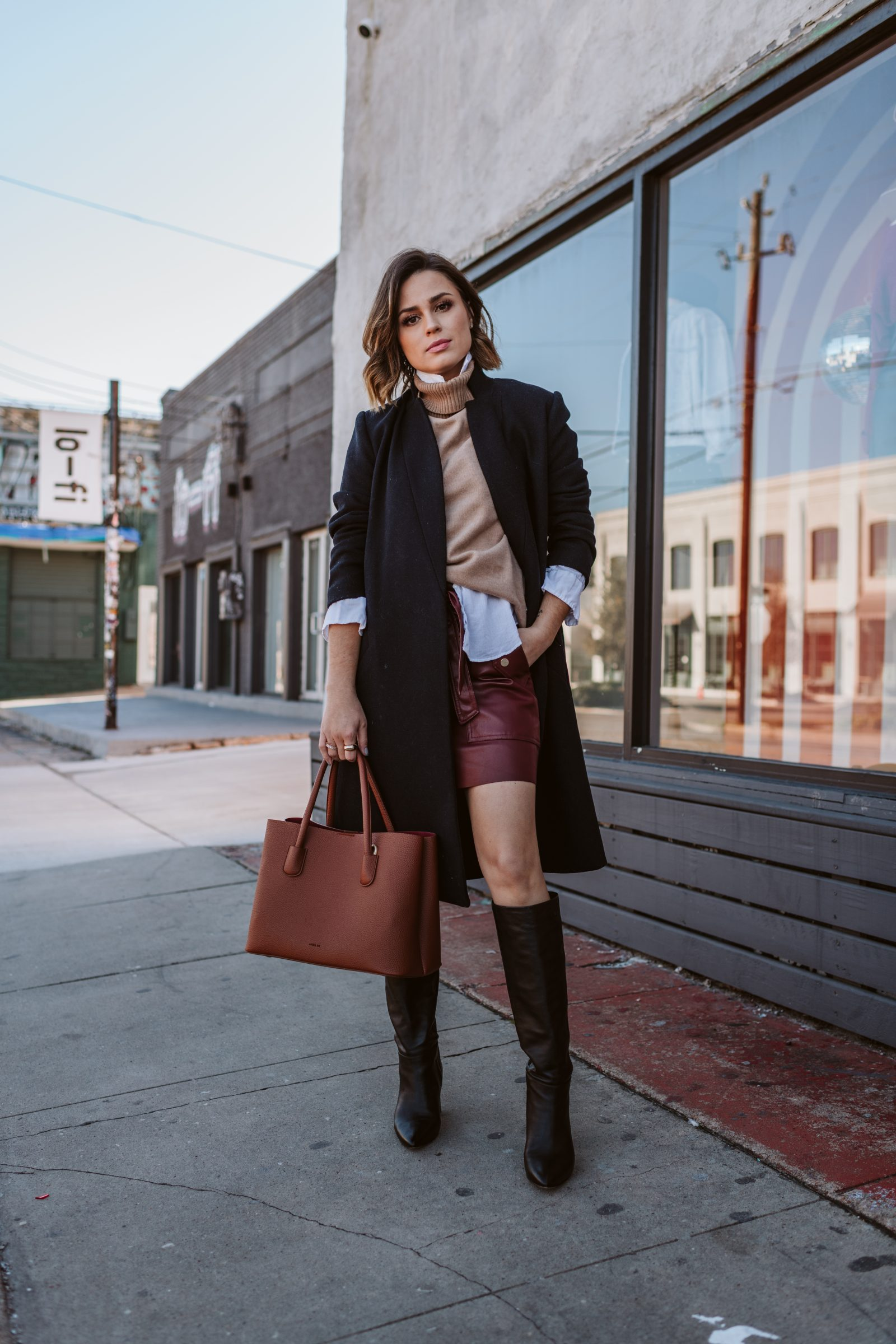 Elly Brown wears Zara faux leather skirt and knee high boots. Wool coat outfit / street style inpso