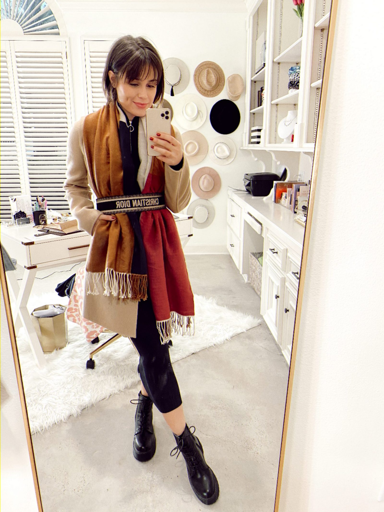 Elly Browns wears a waist belt over her scarf and wool coat.