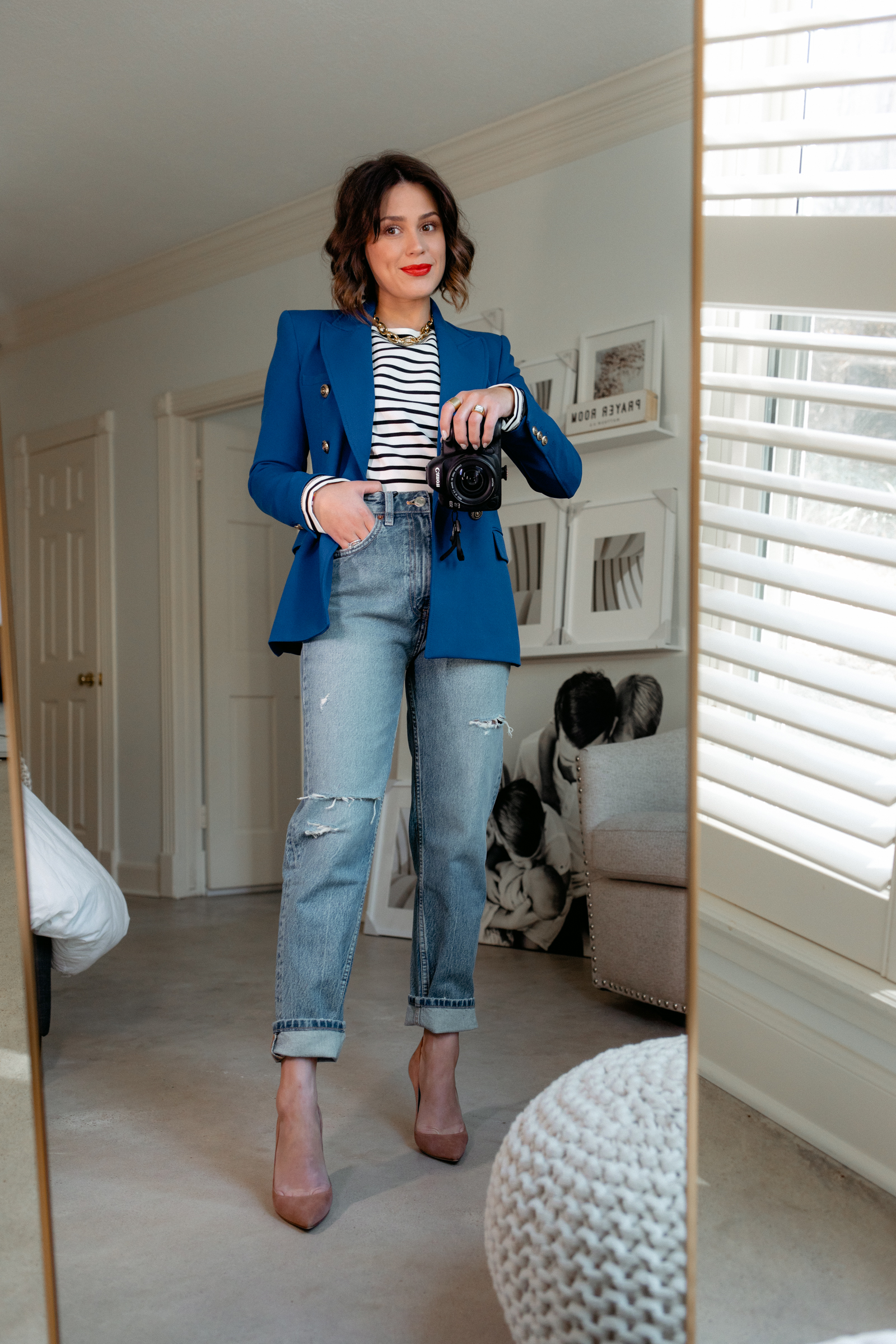 Elly brown wears a navy blue blazer with distressed mom jeans and heels