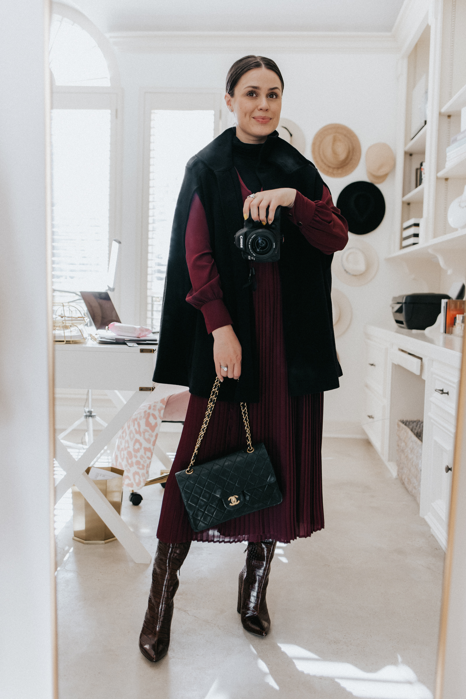 elly brown styles a winter cape coat from zara with a pleated dress and knee high boots