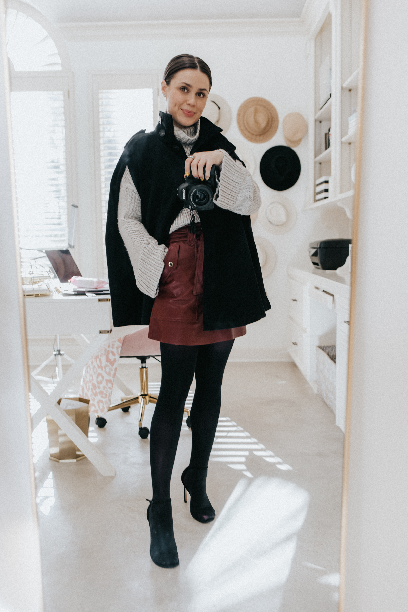 elly brown styles a winter cape coat from Zara with a faux leather skirt, stockings and sandals