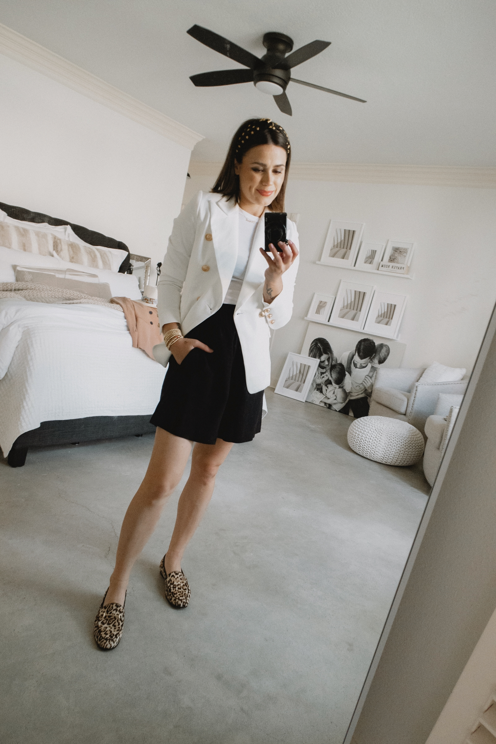 Elly Brown styles a white structured blazer casually with linen shorts and leopard loafers