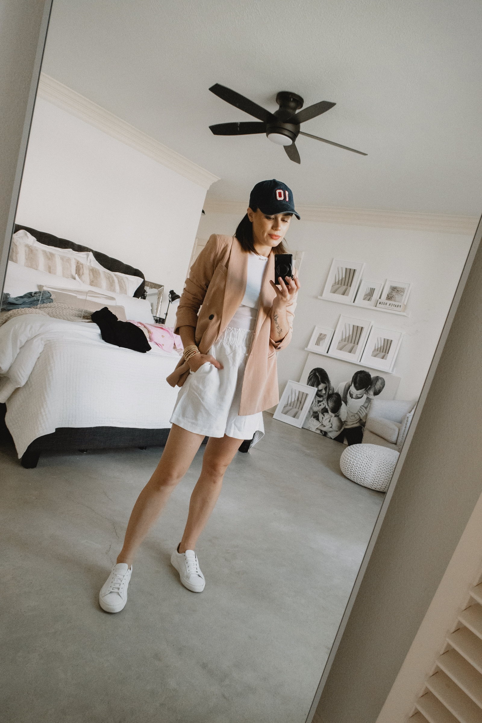 Elly Brown styles linen shorts with a tan blazer and baseball cap outfit