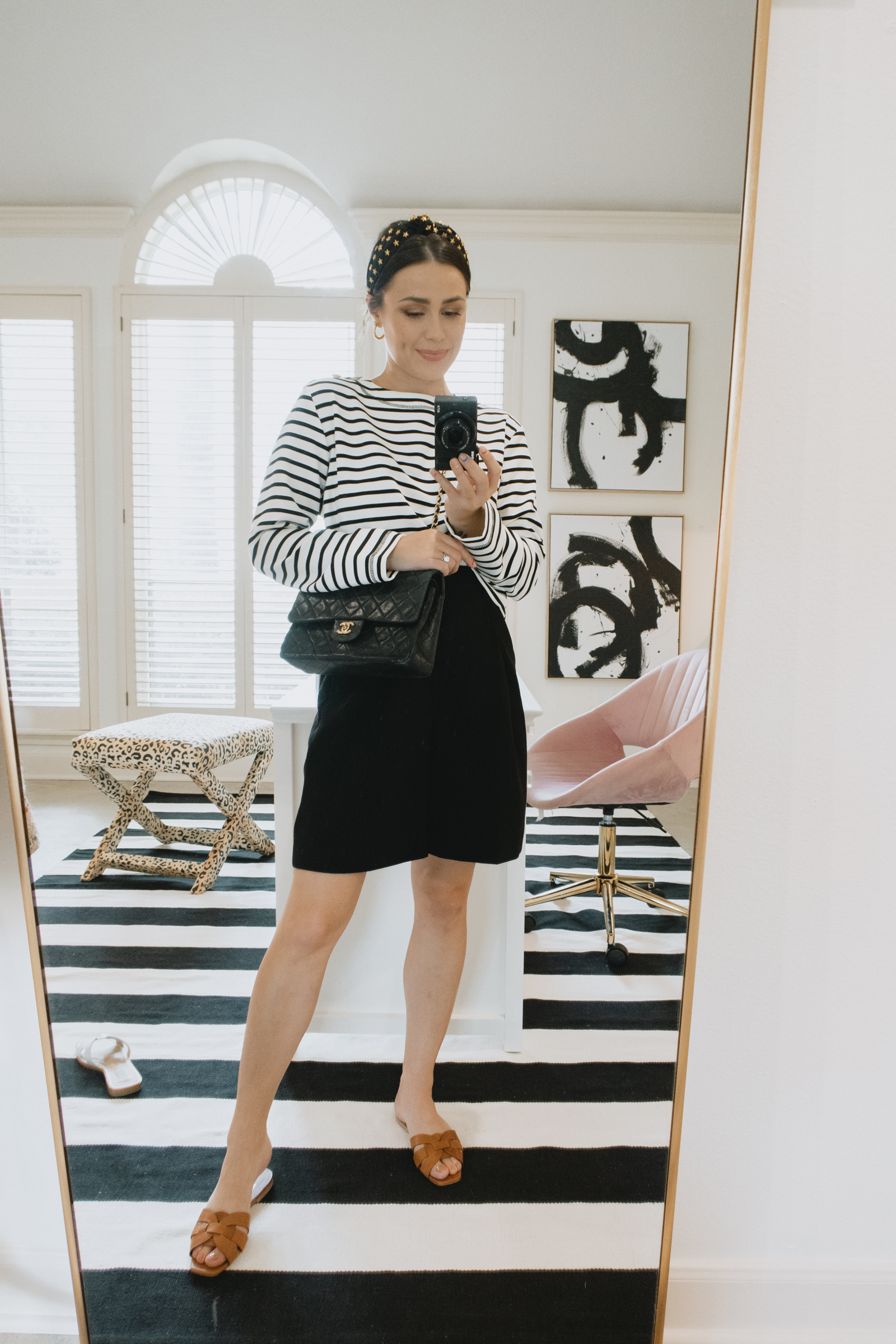 Elly Brown wears bermuda shorts with a stripped tee and brown YSL slides