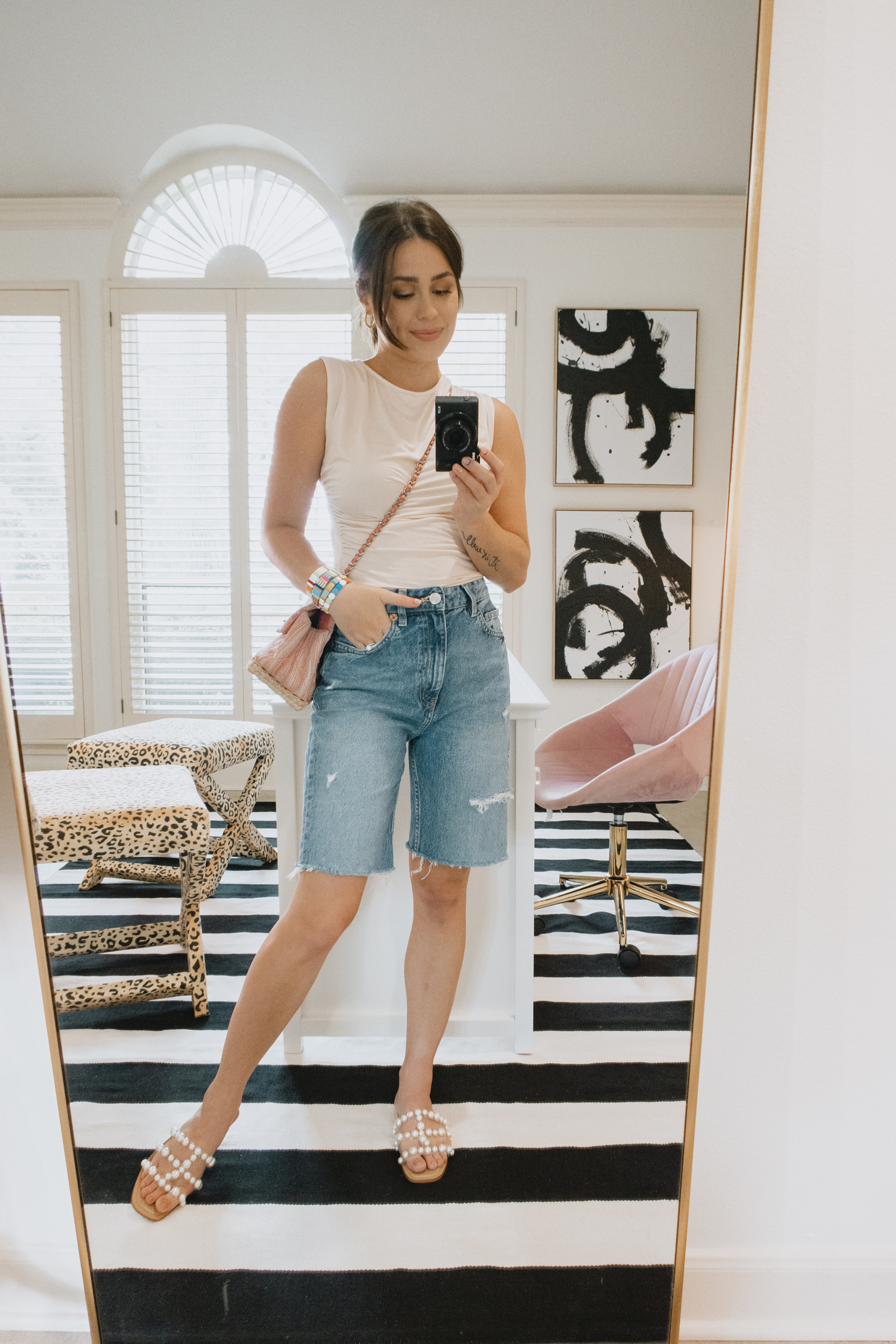 Elly Brown wears black bermuda denim shorts with a simple tank and pearl sandals from Zara