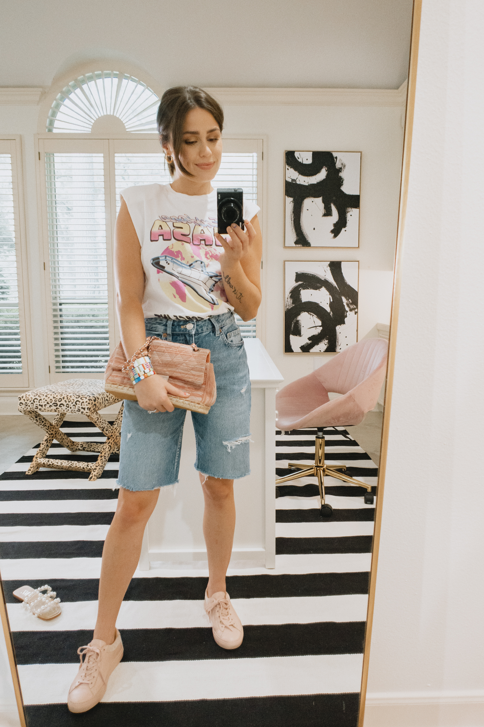 Elly Brown wears black bermuda denim shorts a graphic tee and pink leather sneakers